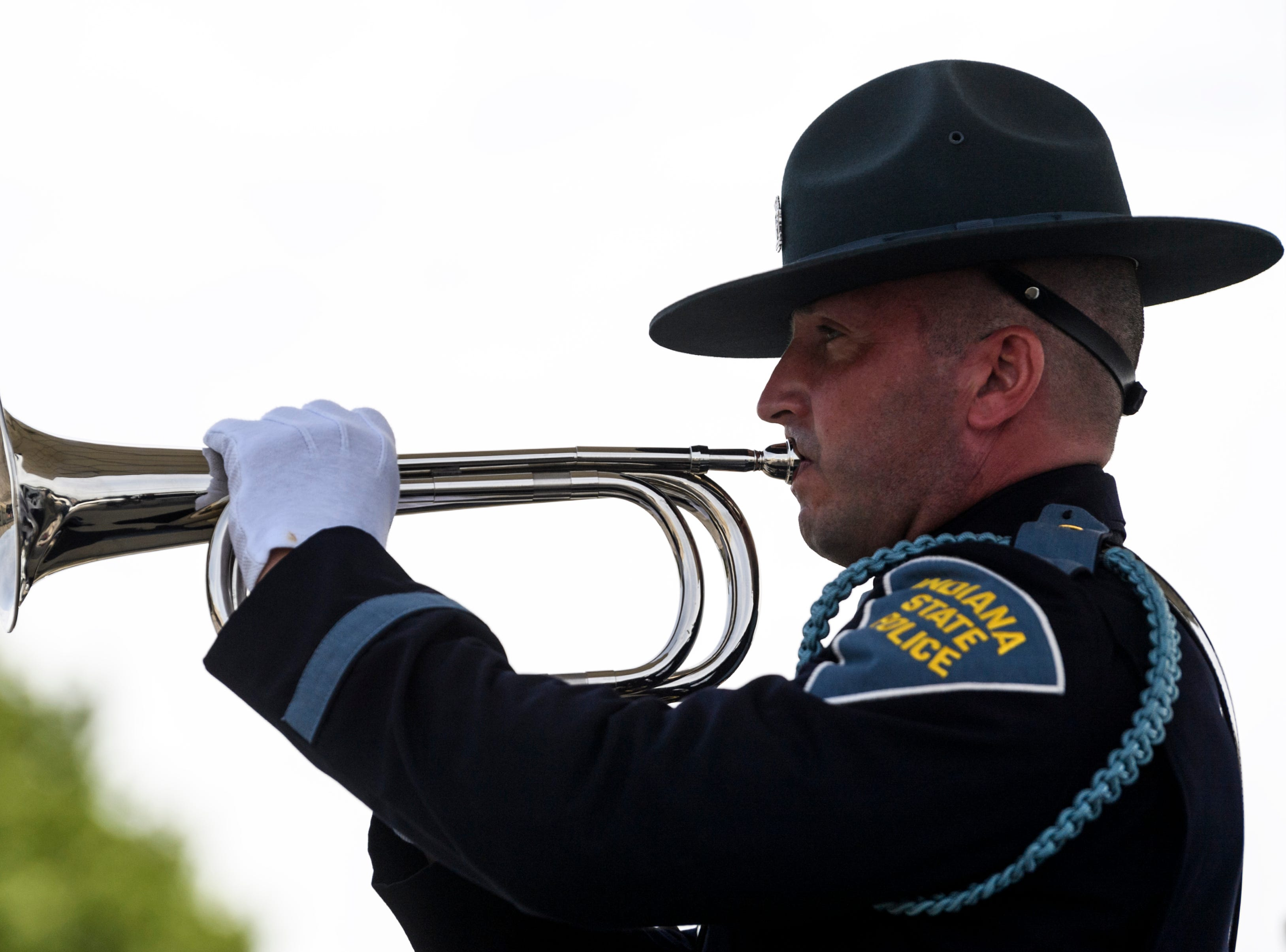 An Indiana State Police officer plays taps to honor the 46 officers who died in the line of duty over the years during the annual memorial service at the ISP Post in Evansville, Ind., Wednesday, May 8, 2019.