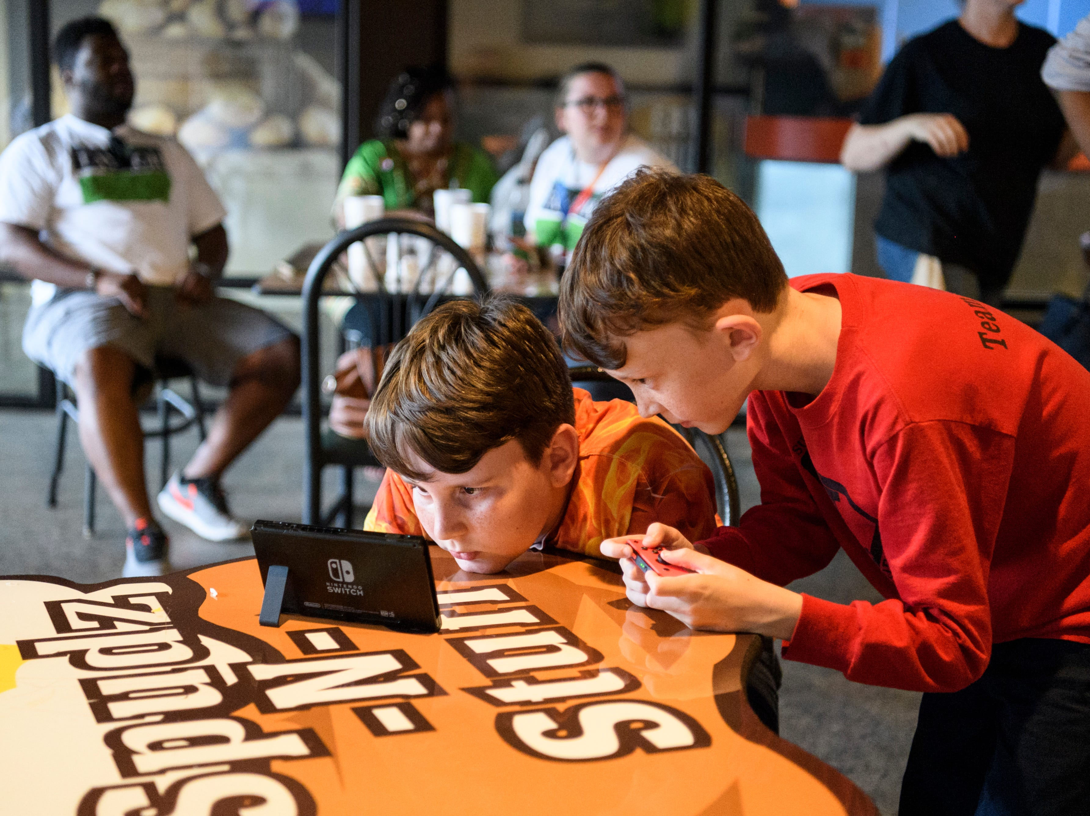 Brothers Sam, left, and Peter Ungar, right, play a game on their Nintendo Switch as adults wait for election results to come in during a watch party at Spudz-N-Stuff on Washington Avenue in Evansville, Ind., Tuesday, May 7, 2019. Their mother Gina Robinson Ungar won one of three democratic at-large city council spots for the upcoming November general election.