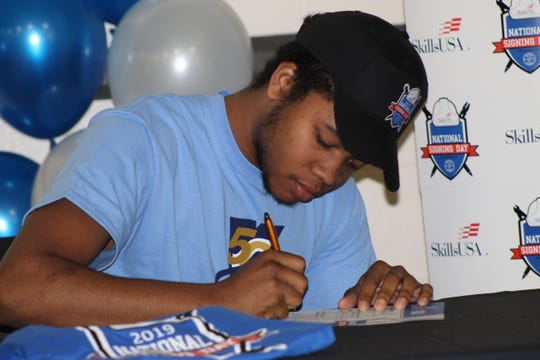 Malcom Burris, a senior at Vanguard signs a letter of national signing day to become a local bricklayer.
