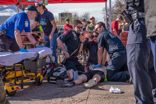 Half marathoner Kyle Woods receives CPR on Sunday morning after collapsing at the finish line of the Colorado Marathon. On Tuesday, he was recovering and got to thank UCHealth paramedic Monique Rose and EMT Greg Harding. They were assisted by paramedic George Solomon, EMT Adam Colclough, reserve EMT Tim Gaines and Poudre Fire Authority battalion chief and firefighter Kevin Waters.