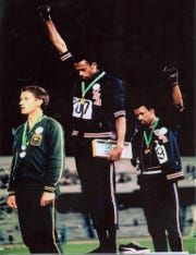 Tommie Smith, center, and John Carlos, right, raise their fists on the medal stand after winning the gold and bronze medals, respectively, in the 200 meters at the 1968 Olympics. Silver medalist Peter Norman of Australia is at left.