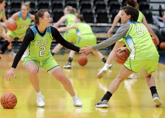 Wisconsin Glo's Mehryn Kraker (2) and Gaby Bronson (20) run a drill during a practice at Menominee Nation Arena in Oshkosh. The professional women's basketball team begins play Friday in Oshkosh.