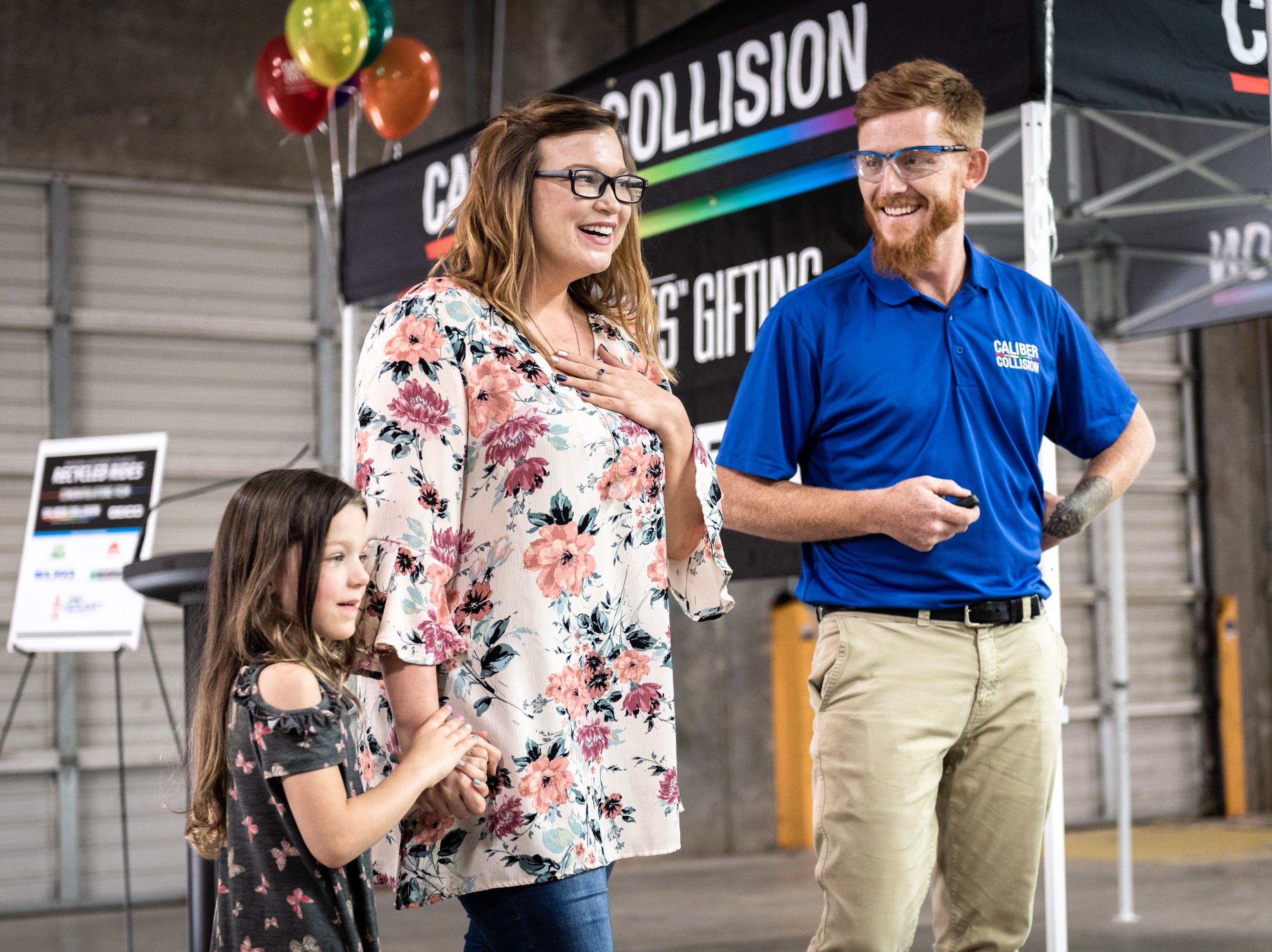 Leah Floyd, 23, with her daughter Avah Floyd, 5, is presented with a 2018 Chevy Cruze at Caliber Collision on Ridge Road in Greenville, Wednesday, May 8, 2019, as part of their Recycled Rides program. Caliber Collision partners with Geico for the program and worked with local nonprofit, AIM who nominated Floyd as the recipient.