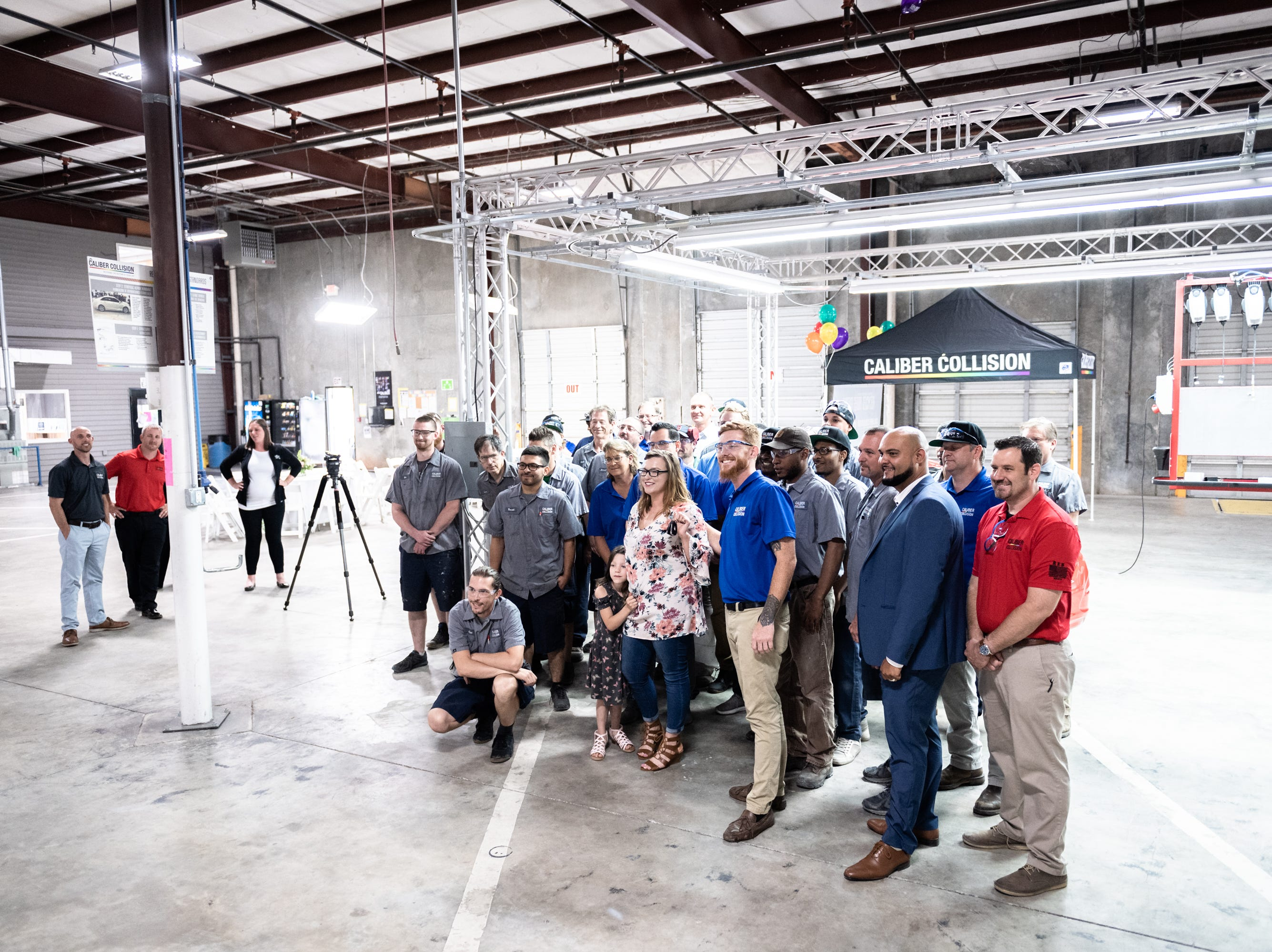 Workers at Caliber Collision on Ridge Road in Greenville, gather with Leah Floyd, 23, a single mother of Anderson, at a ceremony where Floyd was presented with a 2018 Chevy Cruze Wednesday, May 8, 2019, as part of their Recycled Rides program. Caliber Collision partners with Geico for the program and worked with local nonprofit, AIM who nominated Floyd as the recipient.