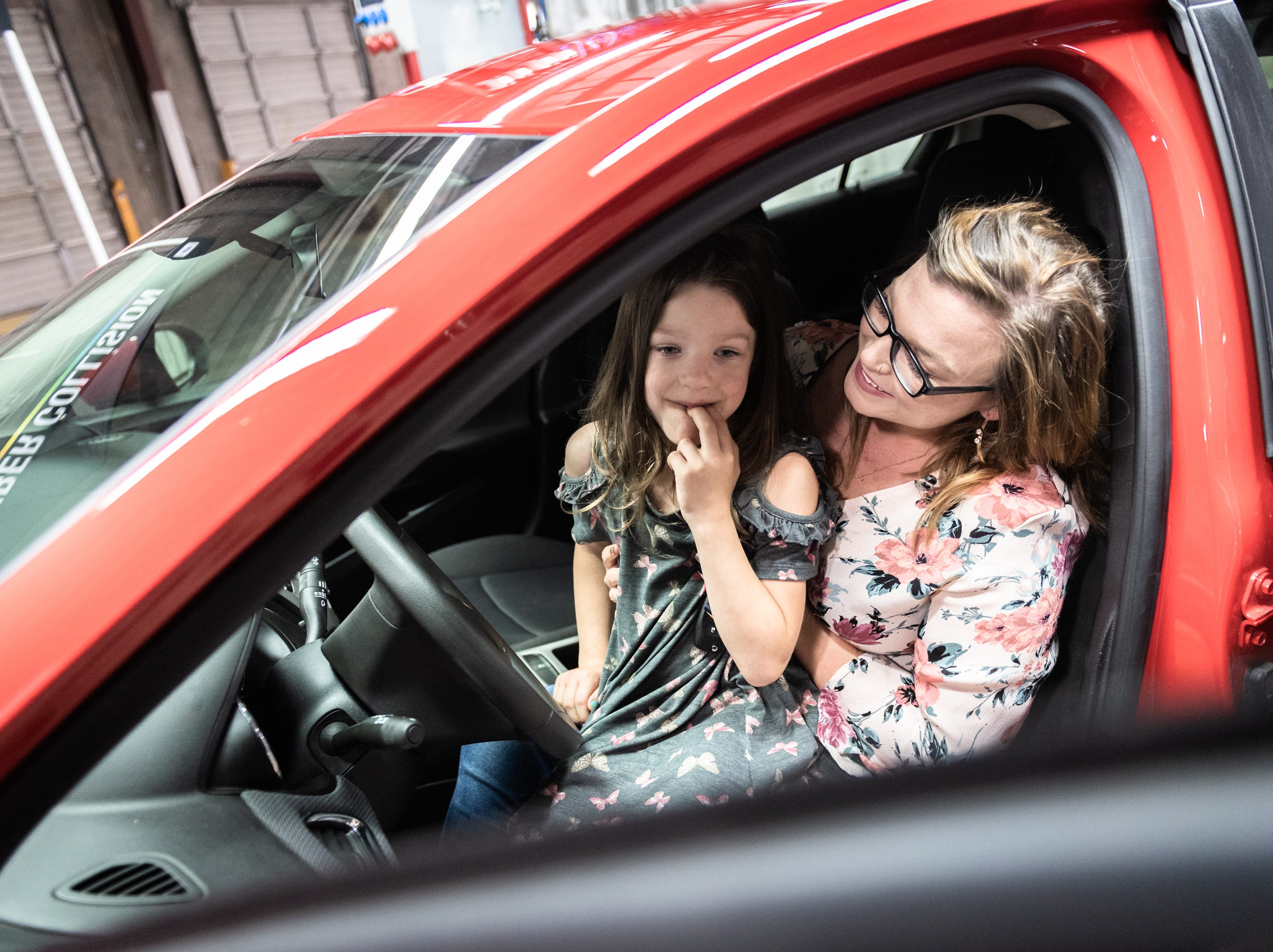Leah Floyd, 23, and her daughter, Avah Floyd, 5, of Anderson, sits in the driver's seat of their new 2018 Chevy Cruze she was presented with at Caliber Collision on Ridge Road in Greenville, Wednesday, May 8, 2019, as part of their Recycled Rides program. Caliber Collision partners with Geico for the program and worked with local nonprofit, AIM who nominated Floyd as the recipient.