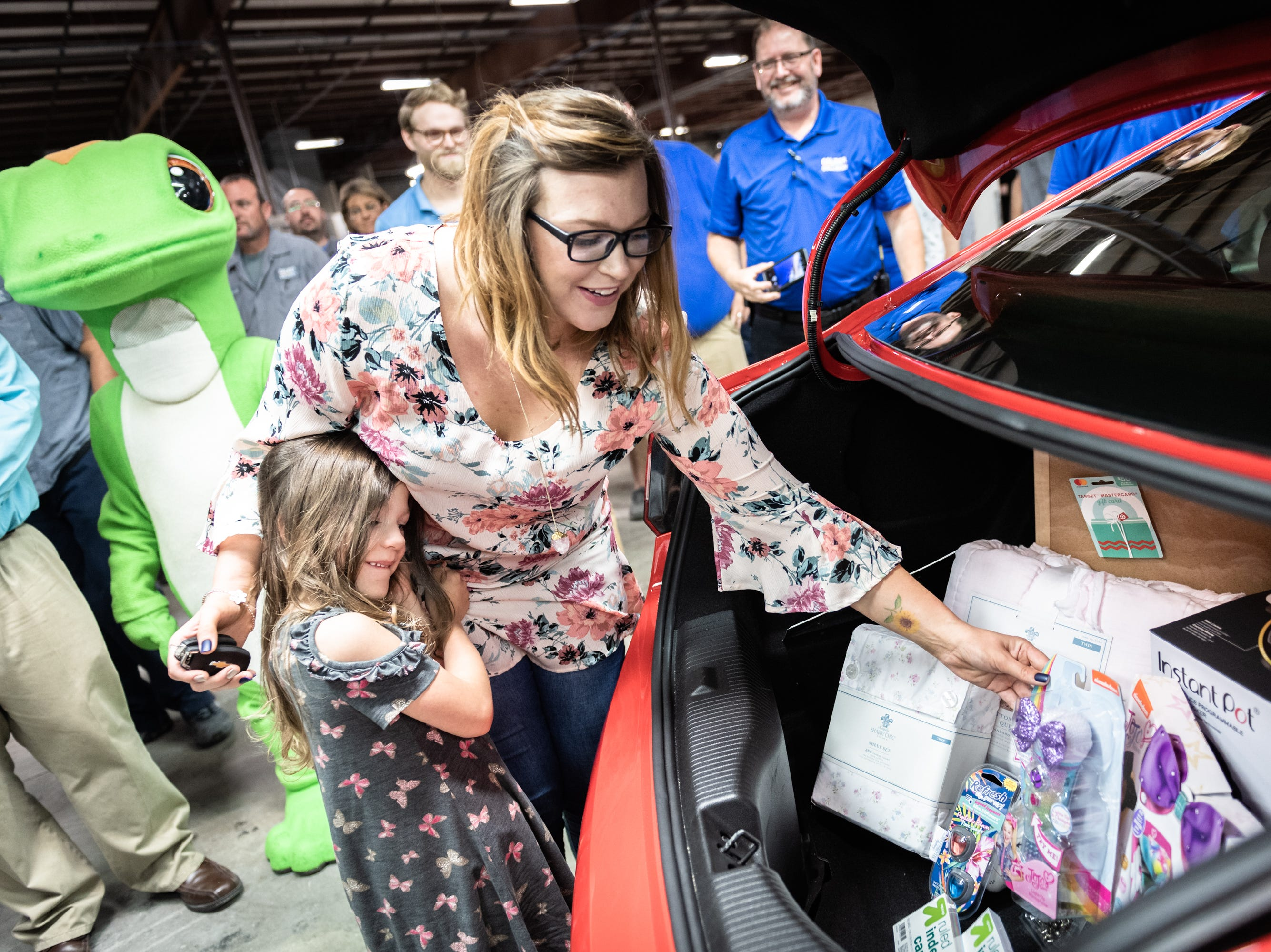 Leah Floyd, 23, and her daughter, Avah Floyd, 5, of Anderson, look at gifts in the trunk of their new 2018 Chevy Cruze she was presented with at Caliber Collision on Ridge Road in Greenville, Wednesday, May 8, 2019, as part of their Recycled Rides program. Caliber Collision partners with Geico for the program and worked with local nonprofit, AIM who nominated Floyd as the recipient.