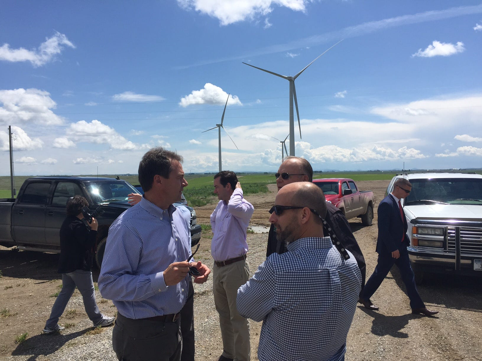 Tribune photo/Karl Puckett Gov. Steve Bullock talks with landowner Marvin Klinker, right, and Allan Frankl of Dick Anderson Construction, foreground, during a visit to the Greenfield wind project near Fairfield.