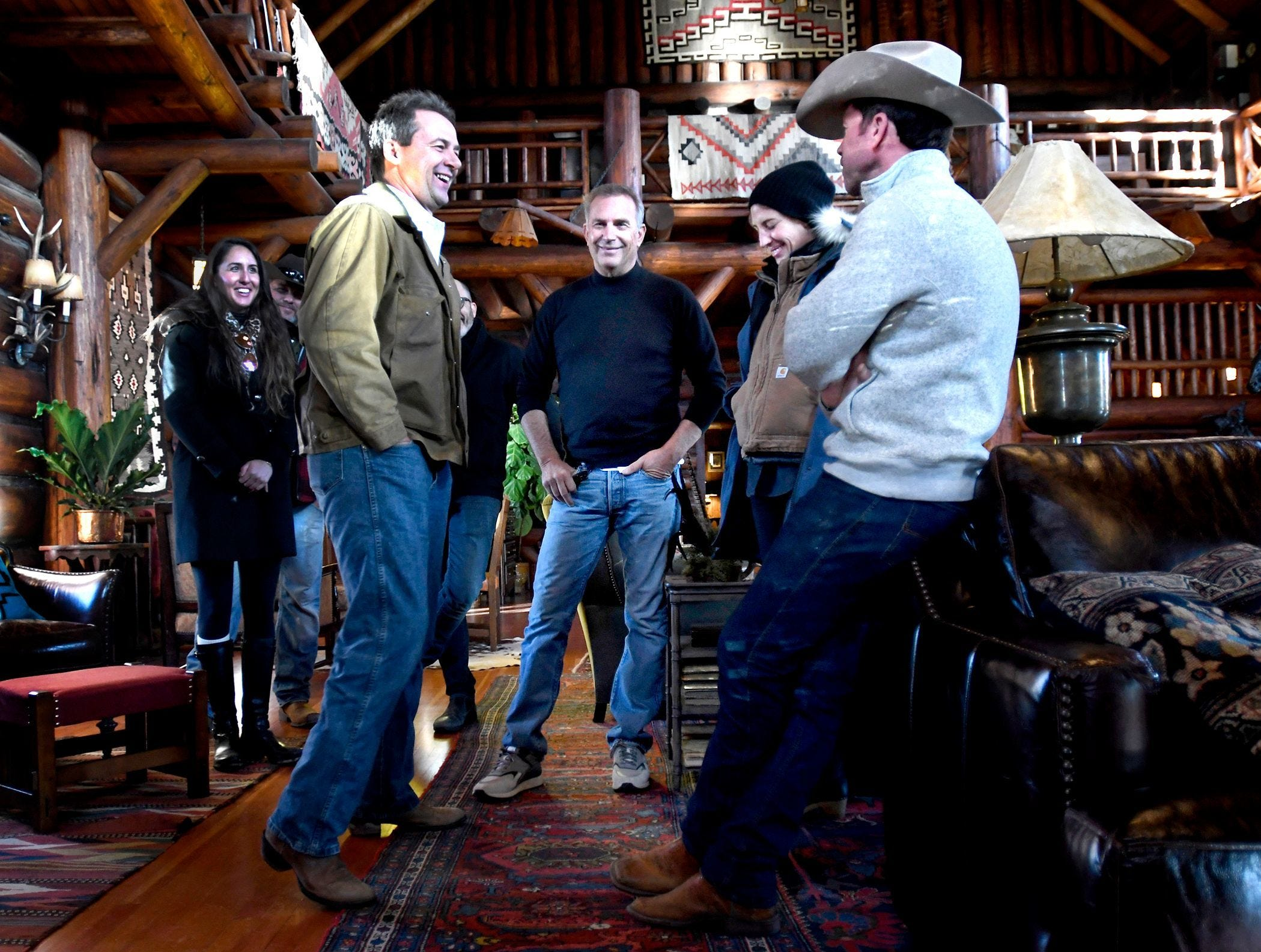 """Gov. Steve Bullock, foreground from left, appears with actor Kevin Costner, production designer Ruth De Jong and writer-director Taylor Sheridan at the Chief Joseph Ranch during a visit to the set of the series ?Yellowstone? in Darby.   Kurt Wilson/The Missoulian via AP In this Dec. 7, 2017 photo, Montana Gov. Steve Bullock, foreground from left, appears with actor Kevin Costner, production designer Ruth De Jong and writer-director Taylor Sheridan in the lodge at the Chief Joseph Ranch during a visit to the set of the television series """"Yellowstone"""" in Darby, Mont. The series is set for release in June. (Kurt Wilson/The Missoulian via AP)"""