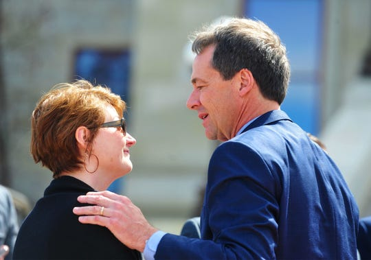 Gov. Steve Bullock talks to Jill Baker after signing into law Senate Bill 160, the Firefighter Protection Act. Baker has been a long-time advocate for legislation to compensate firefighters with work-related illnesses.