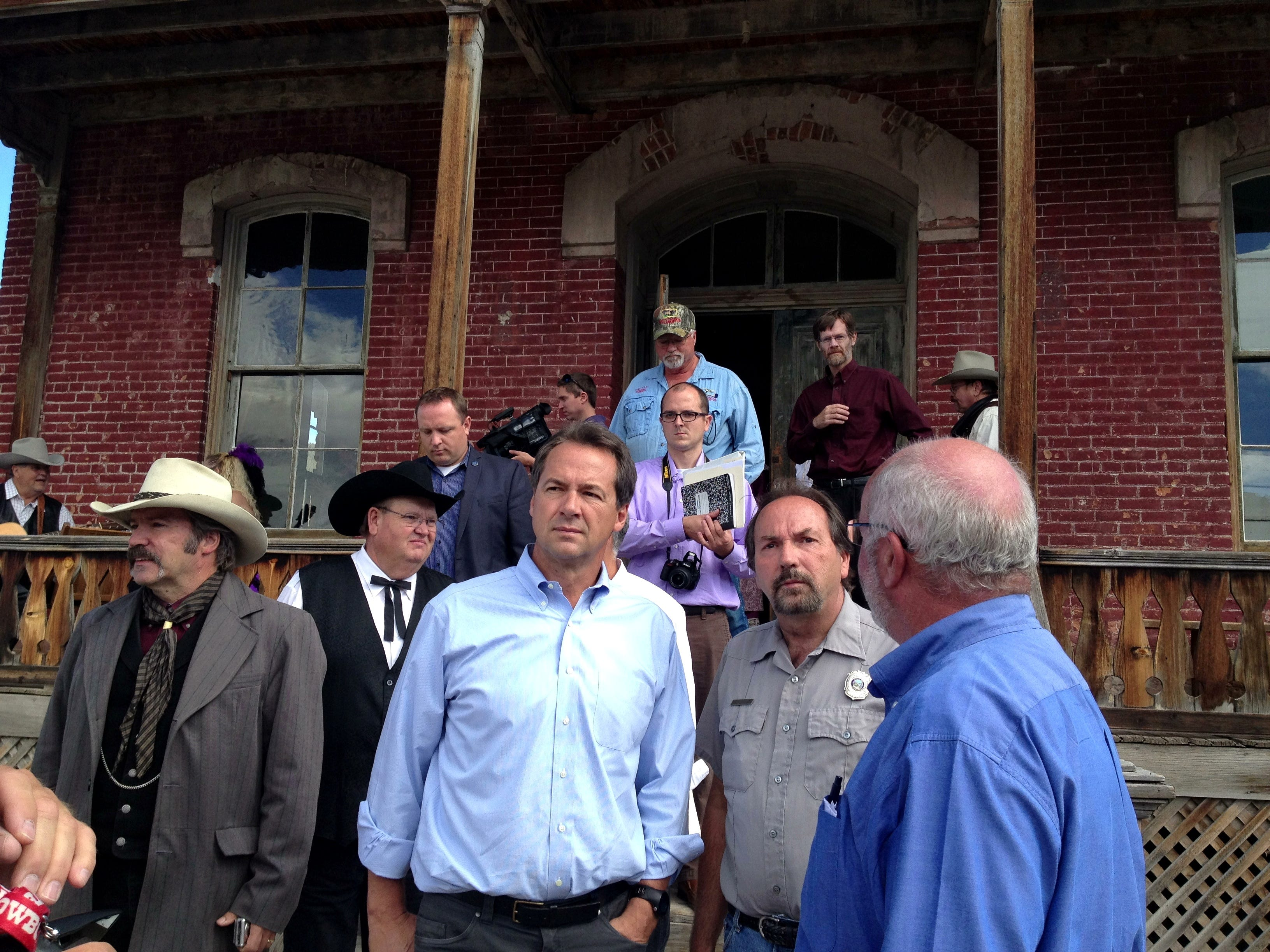 Gov. Steve Bullock (center)  tours Bannack State Park Monday morning. The park has been closed since July 17 when a flash flood damaged most of the ghost town's buildings. The park officially reopened Monday. TRIBUNE PHOTO/ERIN MADISON