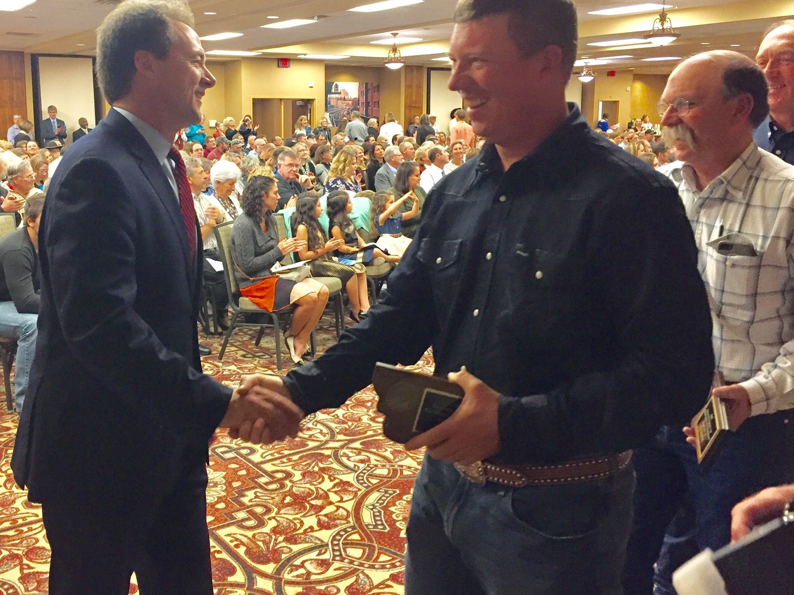 Gov. Steve Bullock, left, congratulates state employees Monday for performance excellence. Gov. Steve Bullock, left, congratulates state employees Monday for performance excellence.