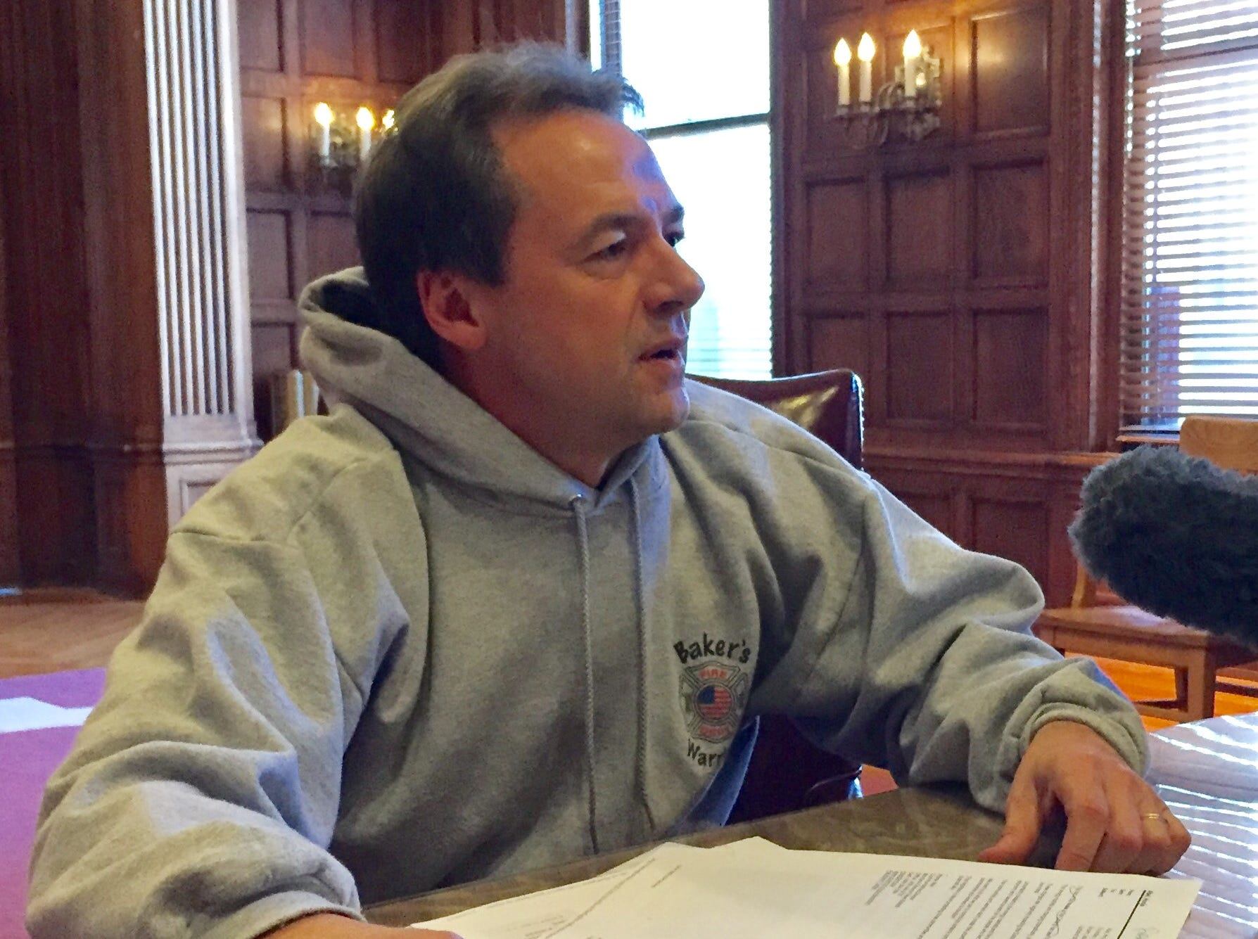 Gov. Steve Bullock wears a Bakers Warriors hoodie Thursday to a news conference.