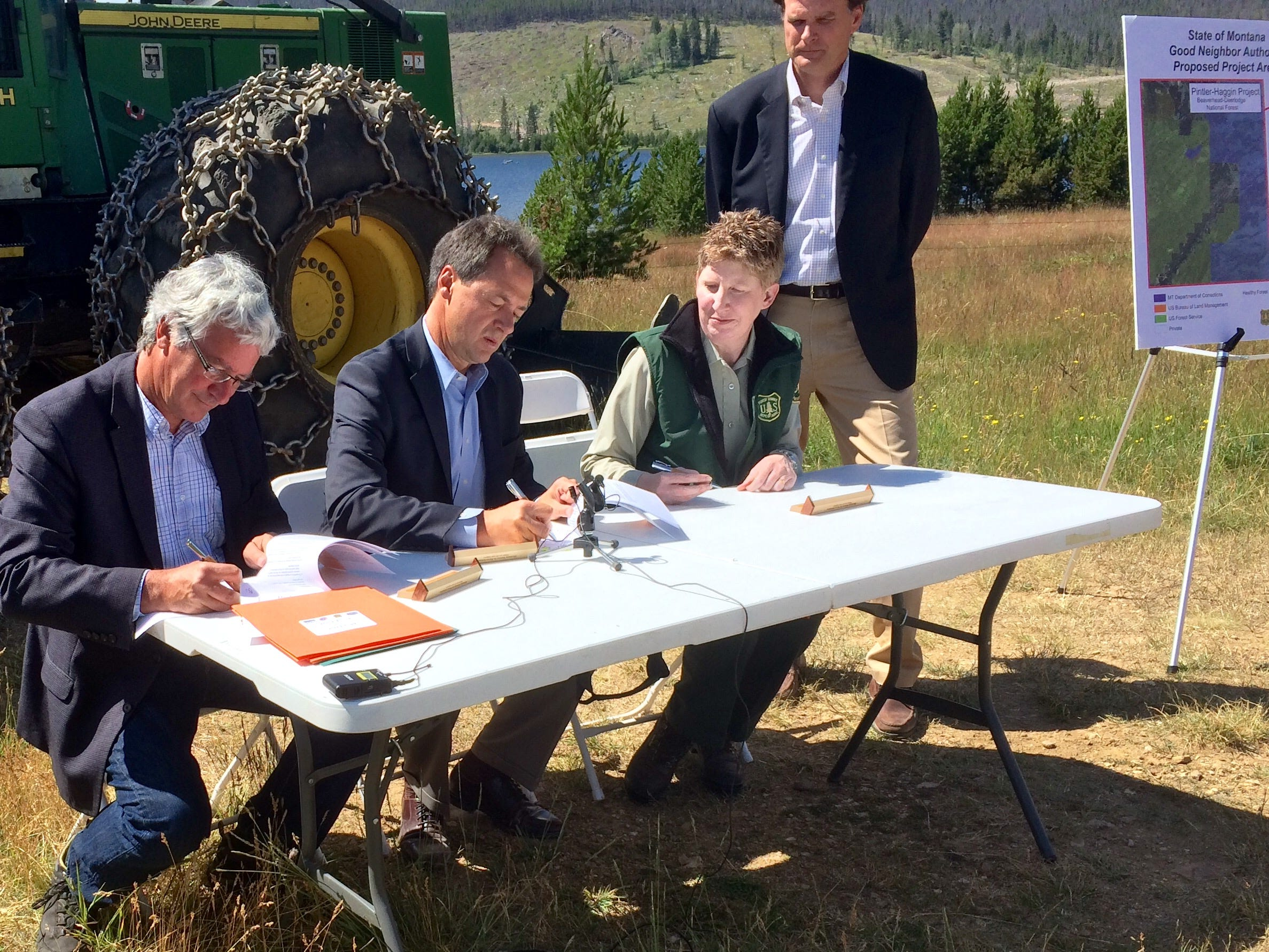 Tribune photo/Phil Drake John Tubbs, left, signs a Good Neighbor Agreement on Monday. Also pictured are Gov. Steve Bullock, Leanne Marten and Robert Bonnie.