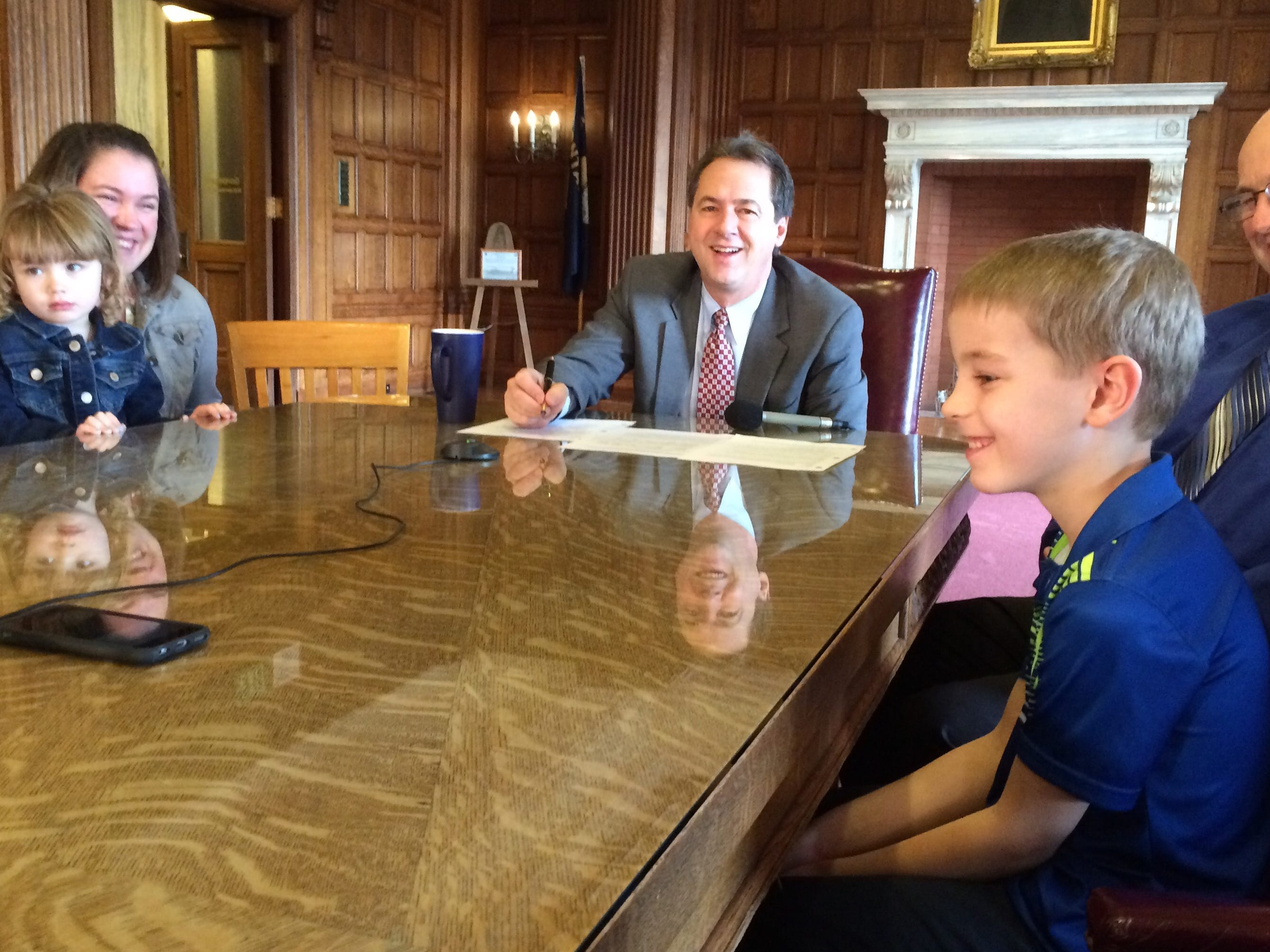 Tribune photo/Phil Drake Luke Kelley (right), 8, smiles Monday as he hears the voice of his mother, Master Sgt. Heather Kelley, coming from the speakerphone. Looking on (from left) are Brooklyn Keighley, 3, and mom Jalyn; Gov. Steve Bullock and Luke?s dad, Randy.