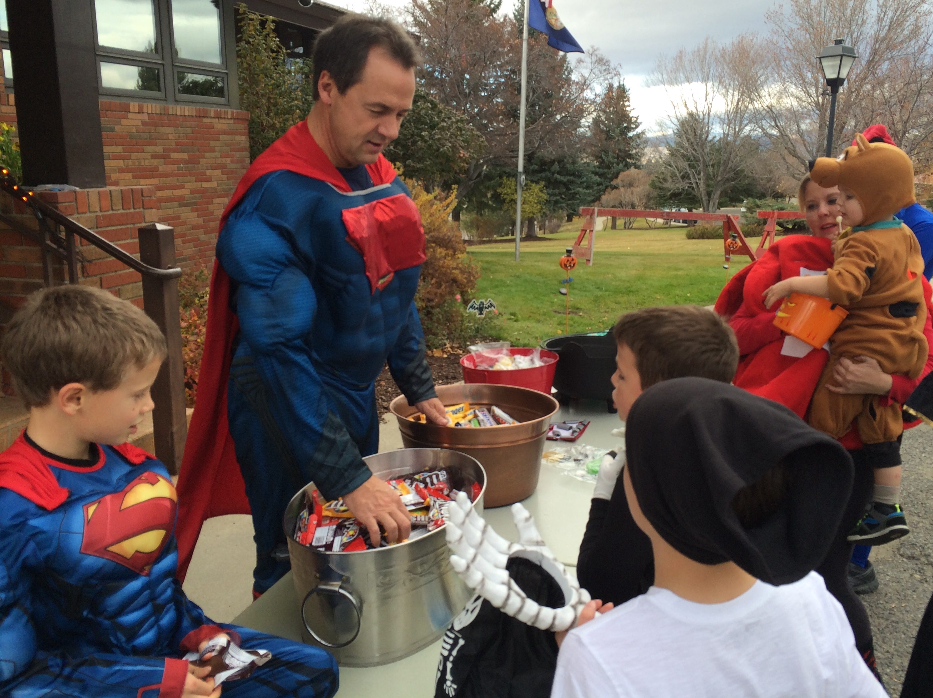 Tribune photo/Phil Drake Super Montana,? aka Gov. Steve Bullock, hands out candy to trick-or-treaters Saturday in front of the governor?s mansion in Helena. The governor held back on giving candy until visitors said trick or treat.