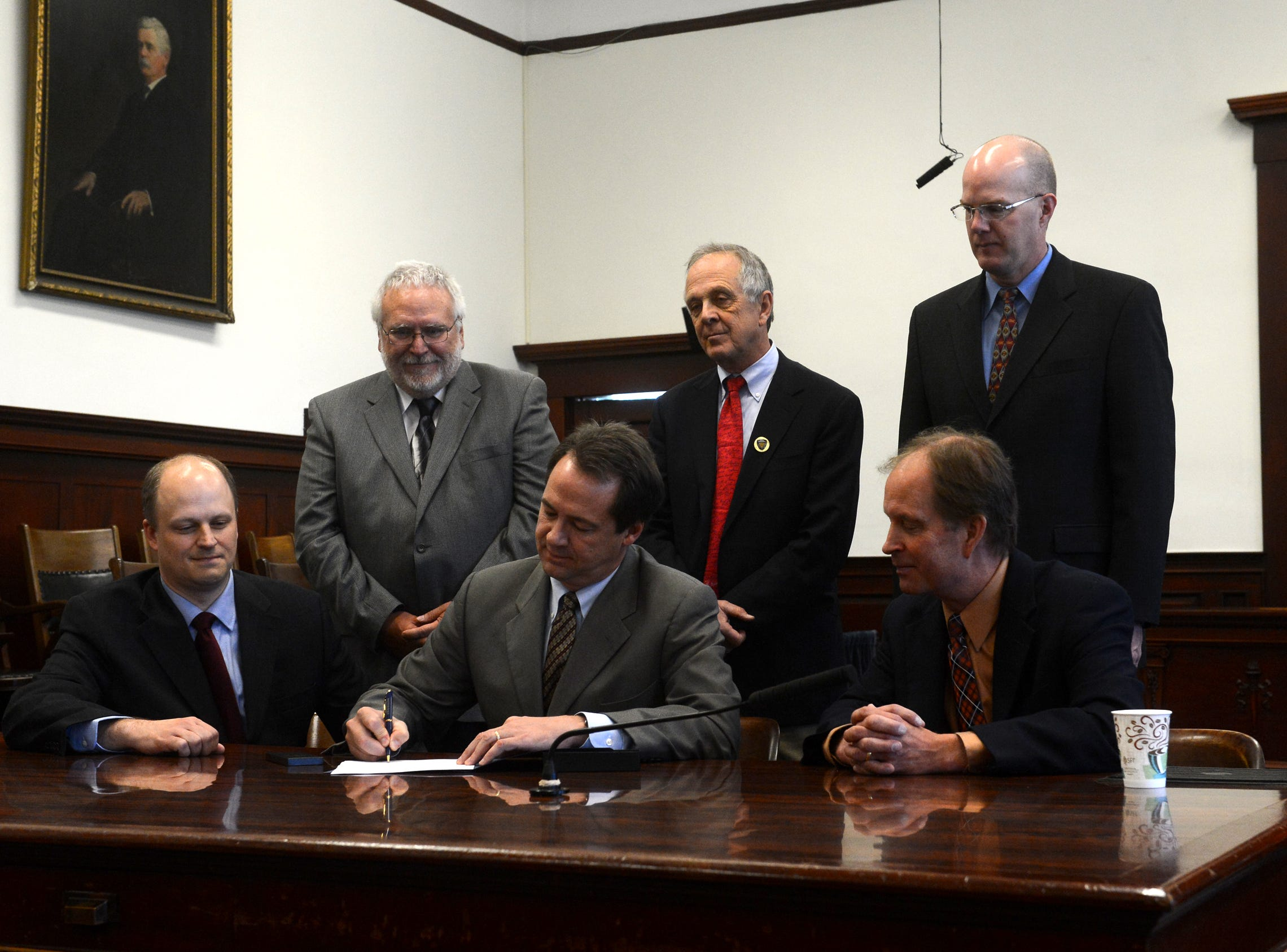 Gov. Steve Bullock signs Senate Bill 160 into law at the Cascade County Courthouse. Govenor Steve Bullock signs Senate Bill 160 into law on Tuesday morning at the Cascade County Courthouse.  Cascade County Attorney John Parker, left, and the bill sponsor Sen. Mitch Tropila, right, look on.  Standing from left: Leo Gallagher, county attorney, Lewis and Clark County; ??Larry Epstein, Glacier County??; Bill Fullbright, county attorney for Ravalli County. TRIBUNE PHOTO/RION SANDERS