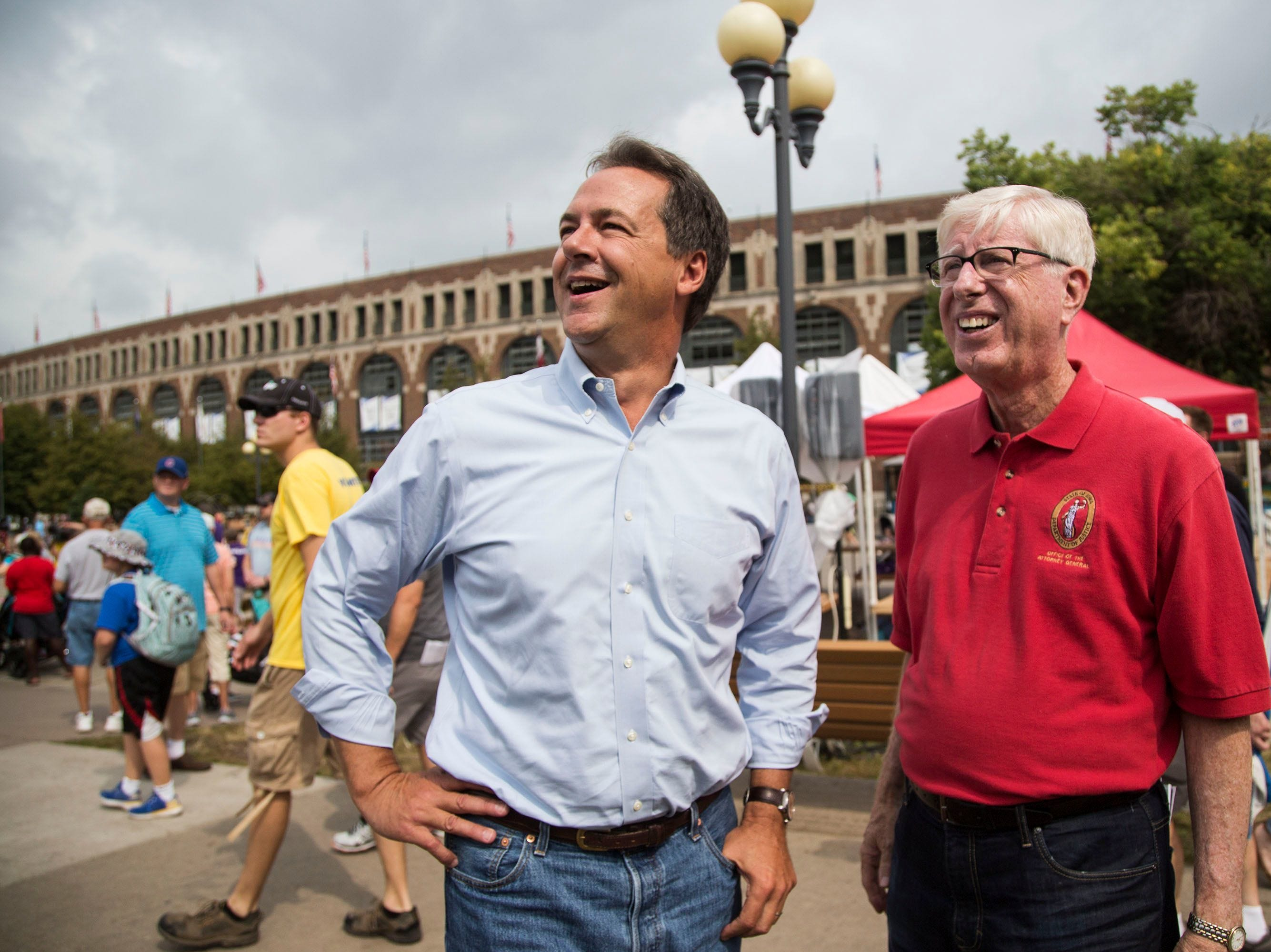 Steve Bullock (left), governor of Montana, stands just off the Grand Concourse of the Iowa State Fair with Iowa Attorney General Tim Miller before speaking at the Des Moines Register Political Soapbox on Thursday.