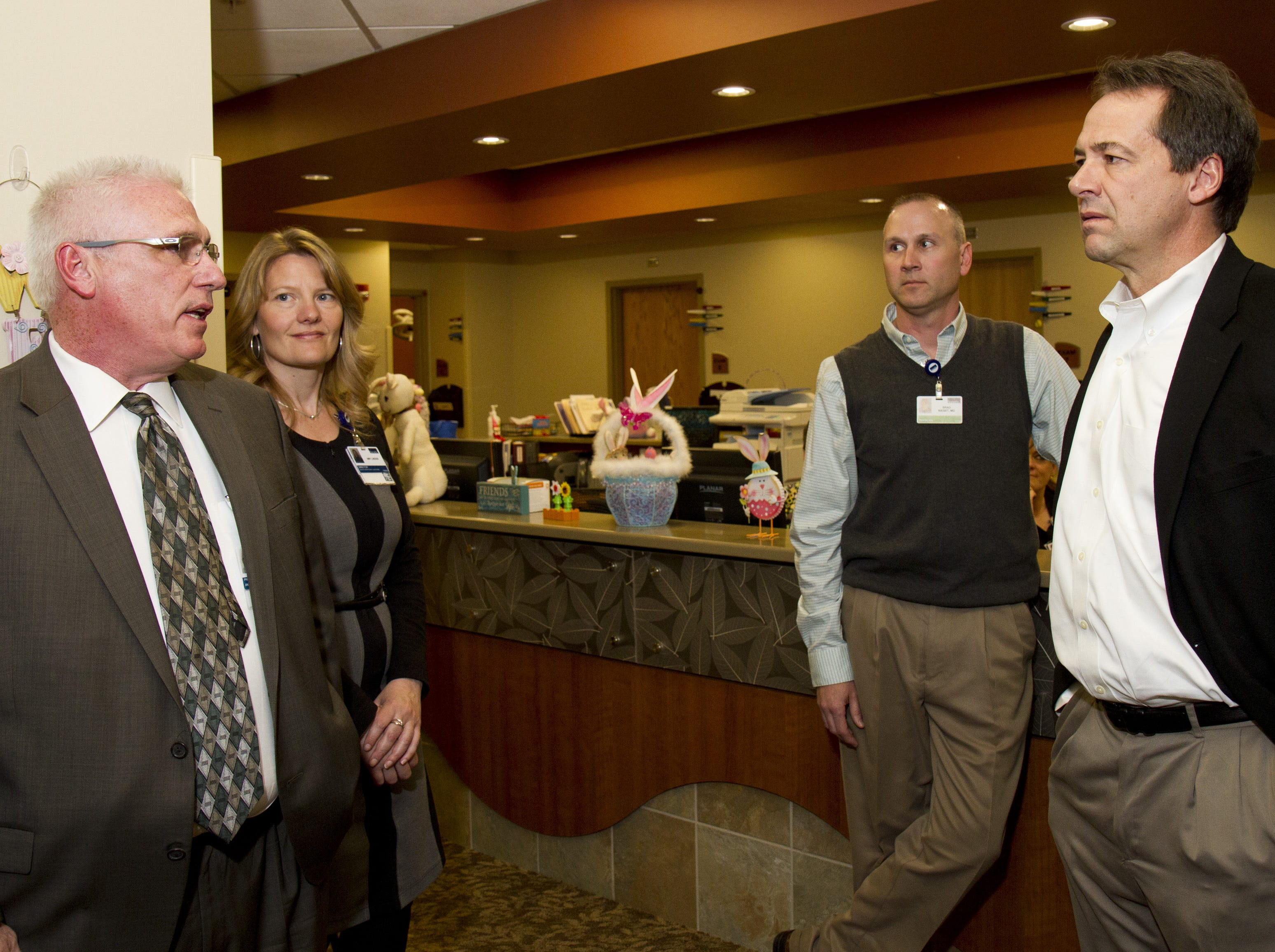 Governor Steve Bullock speaks with Terry Olinger (far left), president of Benefis' Acute Care Group, on the  impact Medicaid expansion could have on the walk-in clinic's patient load.
