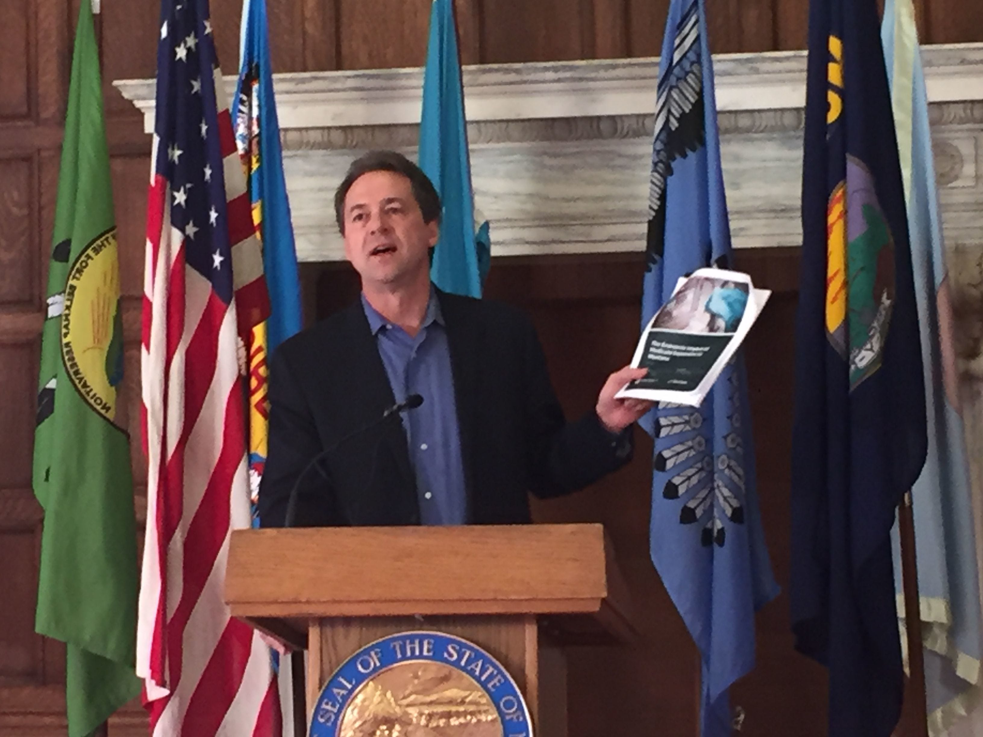 Gov. Steve Bullock holds up a report Wednesday that looks at impacts of Medicaid expansion in Montana. Tribune photo/Phil Drake Gov. Steve Bullock holds up a report Wednesday that looks at impacts of Medicaid expansion in Montana.