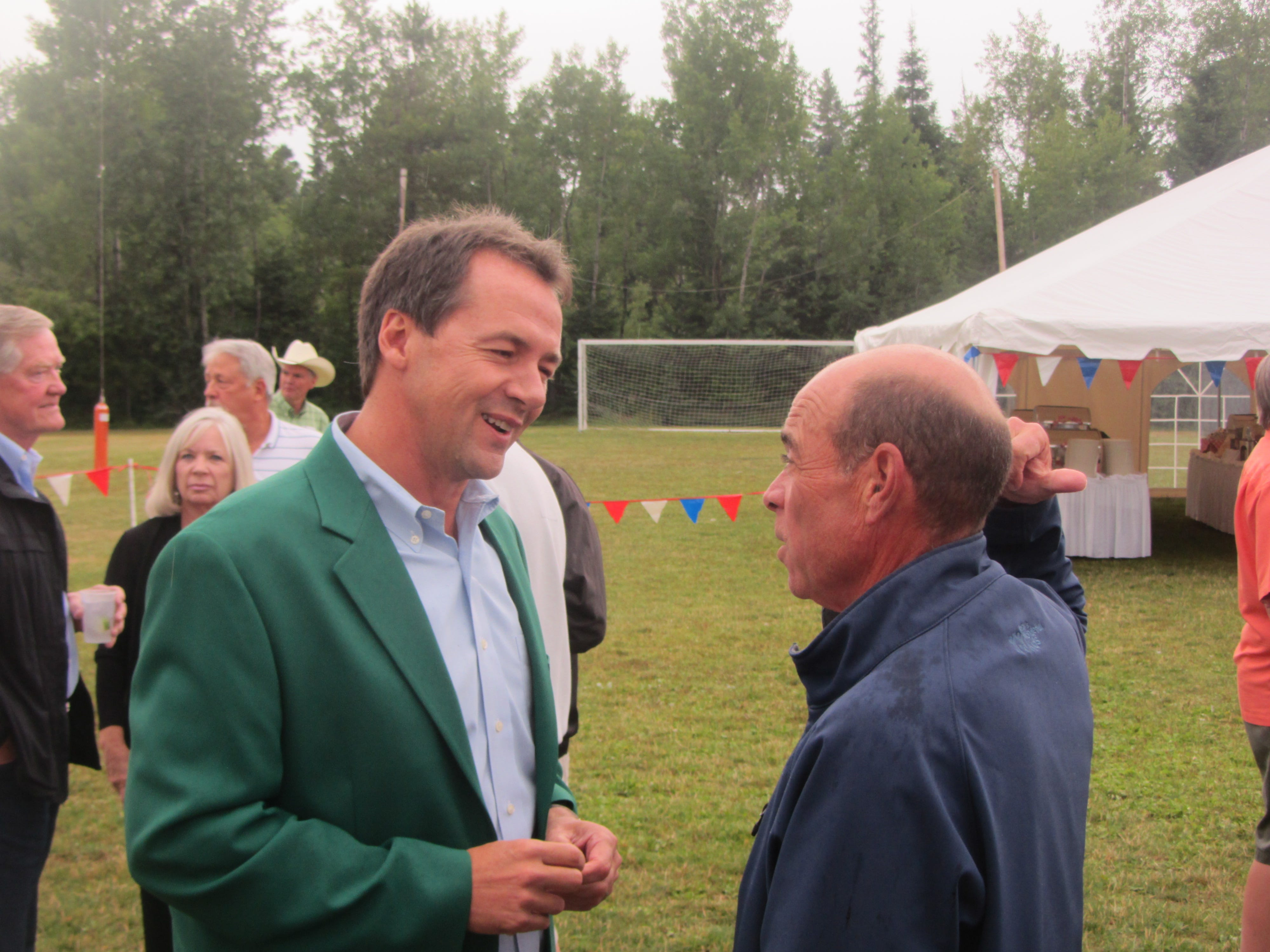 Gov. Steve Bullock visits with Montana Chamber of Commerce Foundation President Rick Reid at the Govenors' Cup golf tournament Thursday night in Whitefish. The chamber gives governors green jackets. Many statewide office holders and legislators attend. TRIBUNE PHOTO/PETER JOHNSON