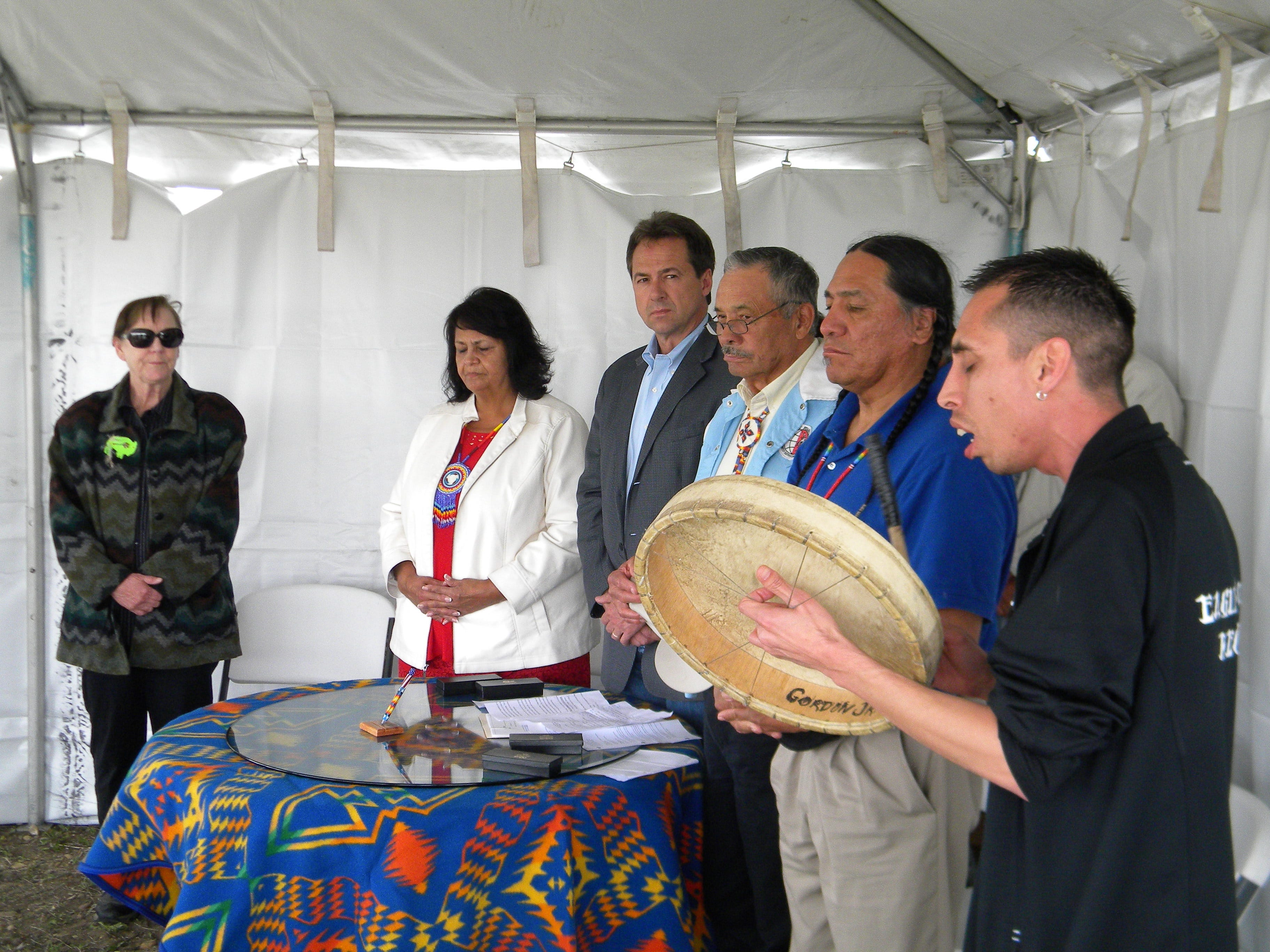 Nakoa Heavy Runner, right, sings  just before Gov. Steve Bullock signed a measure expanding youth suicide prevention efforts. Nakoa Heavy Runner sings an honor song Wednesday at the Fort Peck Tribes' Turtle Mound Buffalo Ranch just before Gov. Steve Bullock signed a measure expanding youth suicide prevention efforts in Montana's tribal communities. From left, Rep. Bridget Smith, D-Wolf Point, Fort Peck Vice Chairwoman Patt Iron Cloud, Gov. Steve Bullock. Tribal Chairman A.T. Stafne and Sen. Jonathan Windy Boy, D-Box Elder.