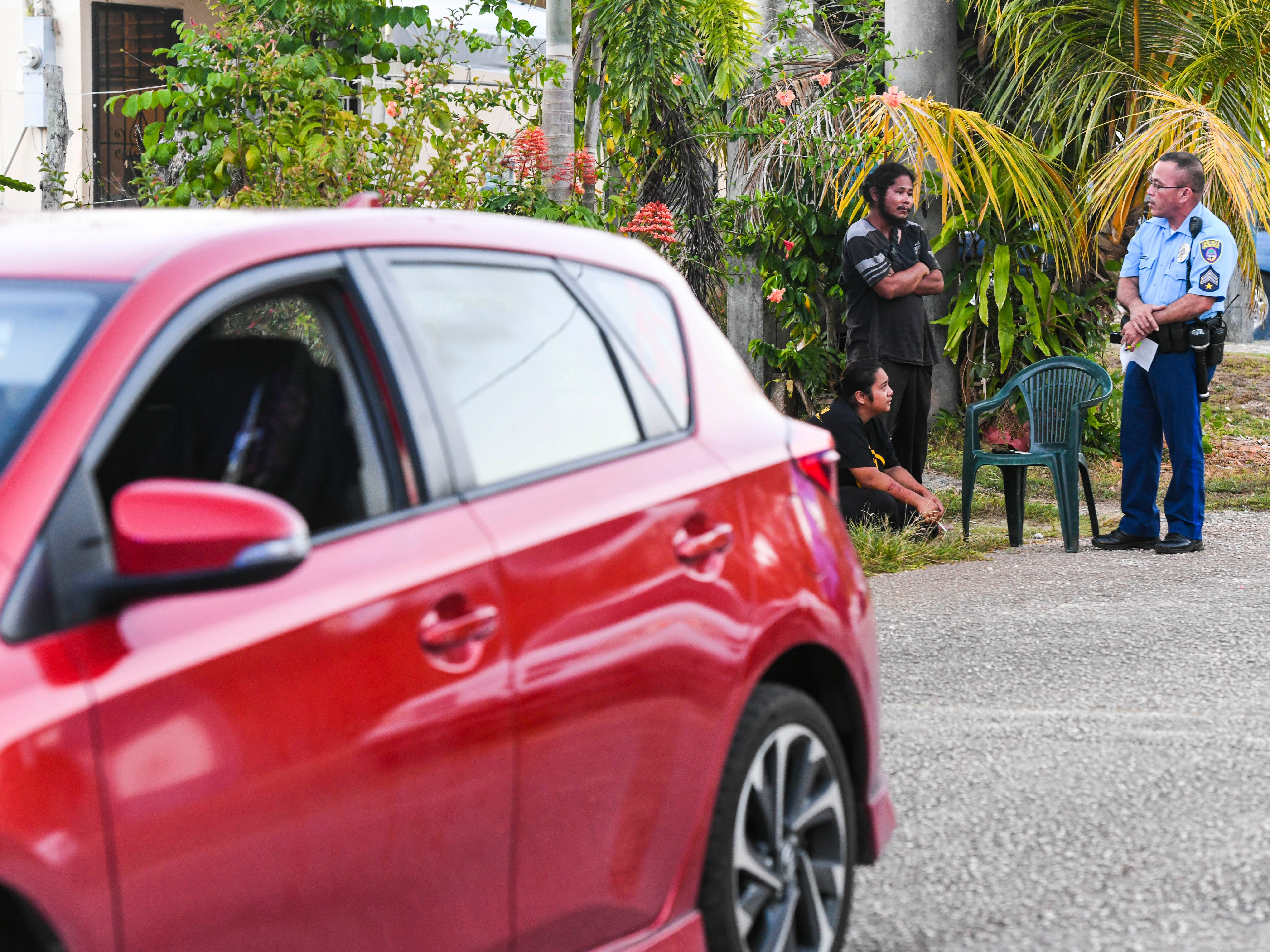 Guam Police Department Officer Jeb Santo Tomas speaks with Ewily Risa, seated, and another individual, during a fatal auto-pedestrian incident in Dededo on the evening of Wednesday, May 7, 2019. Four-year-old Jericho Zion David, died after being struck in front of his family's home, by a Red Toyota Corolla driven by Risa,