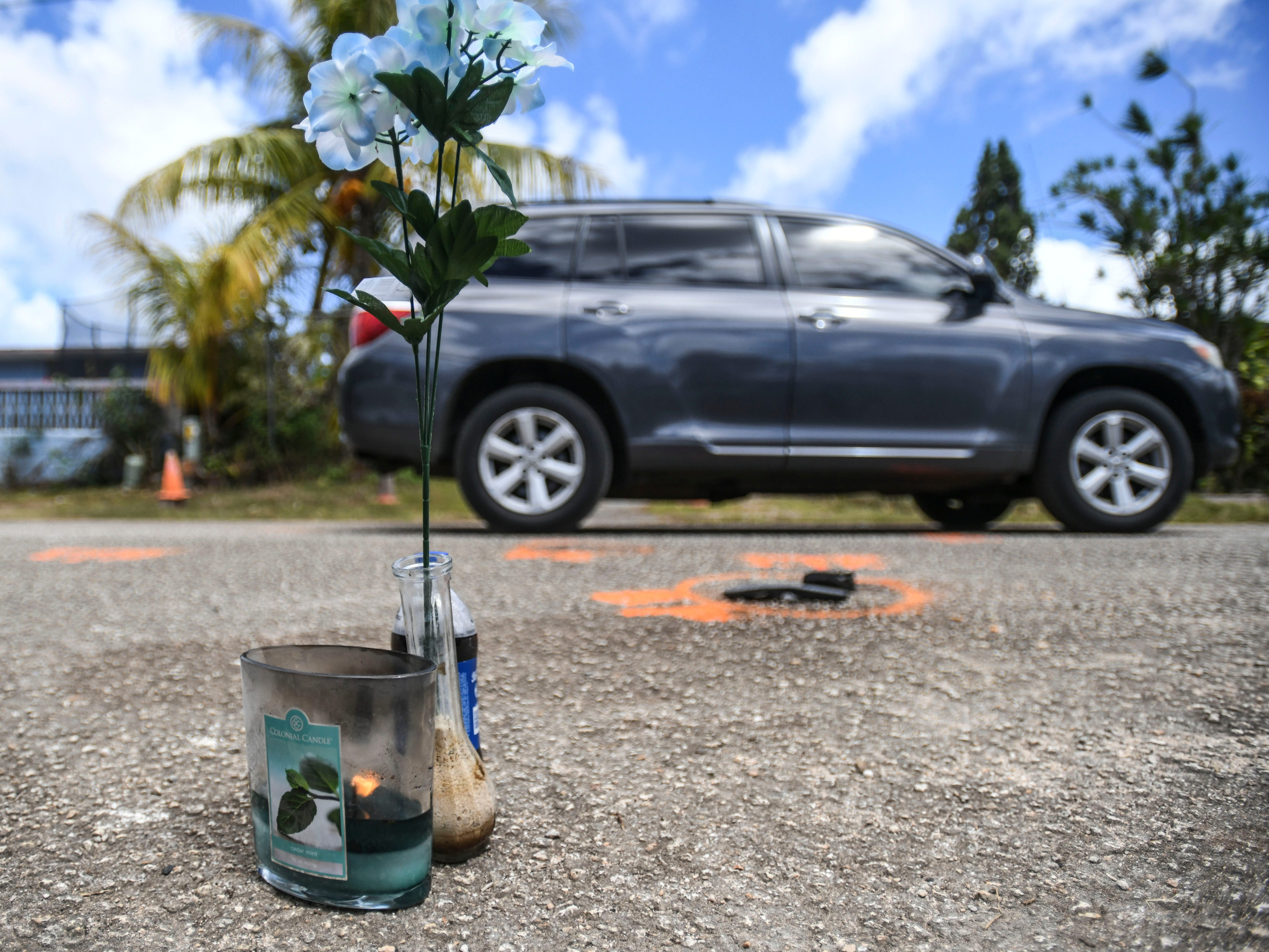 A vehicle passes a solemn arrangement of silk flowers, a candle and a soft drink, set near painted road markings on May 8, 2019, made by police investigators the previous evening at the scene of an auto-pedestrian incident in Dededo. On May 7, 2019, four-year-old nephew, Jericho Zion David, died after being struck by a motorist driving in front of the family's residence.