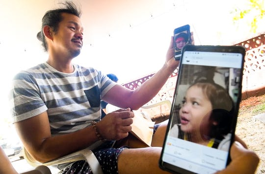 Emotions overcome Enrique David, as he recalls images of his son, Jericho Zion David, on his mobile phone and his sister, Kathleen David, plays a recorded video of the boy, outside the family's Dededo home on May 8, 2019. The four-year-old toddler died, in front of the family's residence the previous evening, after being struck by a passing motorist.