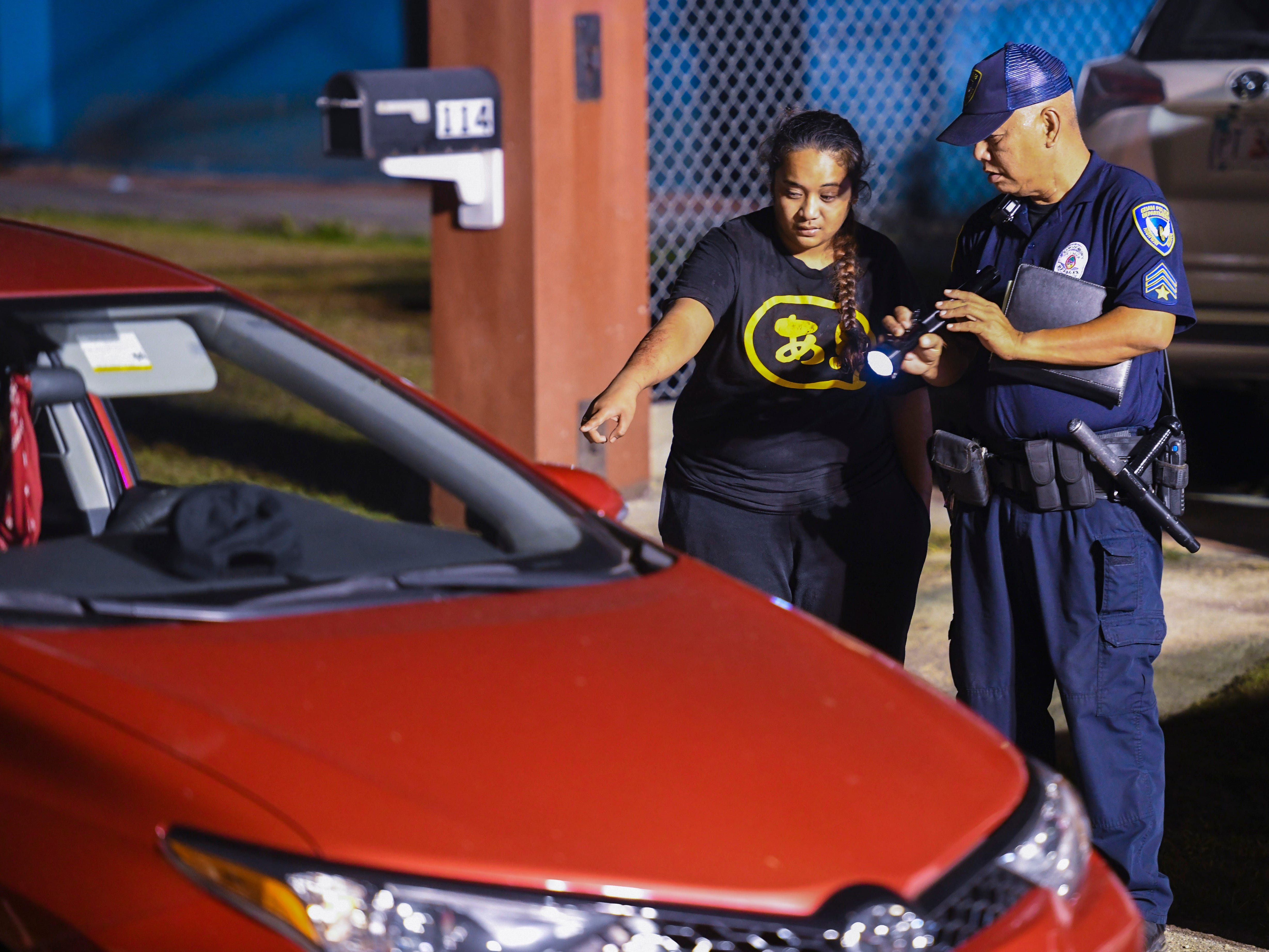 Vehicle operator Ewily Risa, left, assists a Guam Police Department officer during an investigation of a fatal auto-pedestrian incident in Dededo on the evening of Wednesday, May 7, 2019. Four-year-old Jericho Zion David, died after being struck in front of his family's home.