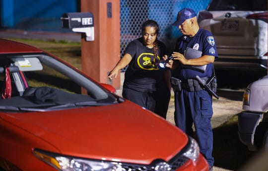 Vehicle operator Marleen Risa Ewily, left, assists a Guam Police Department officer during an investigation of a fatal auto-pedestrian incident in Dededo on the evening of Wednesday, May 7, 2019. Four-year-old Jericho Zion David, died after being struck in front of his family's home.