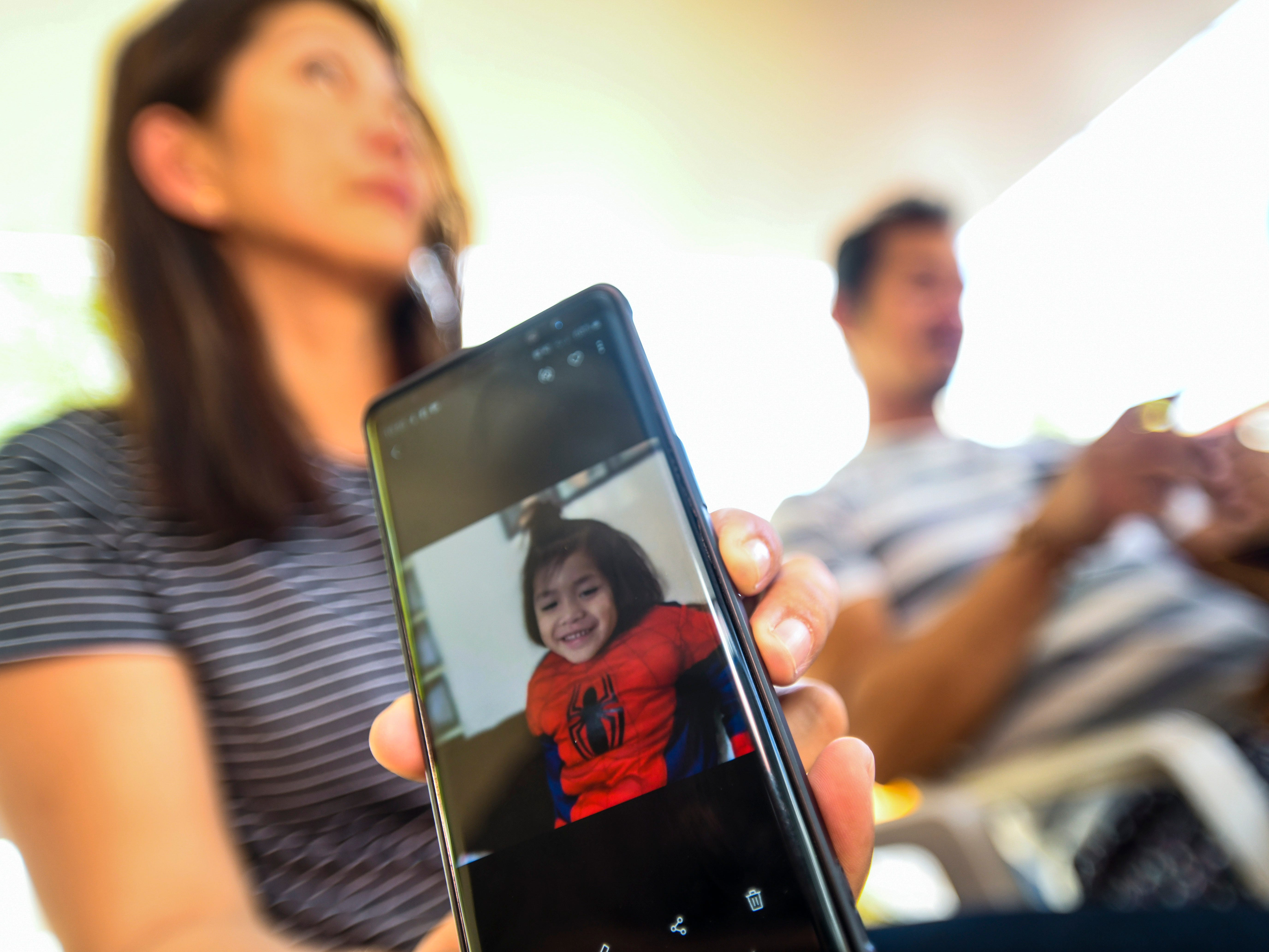 Kathleen David shares a Spiderman image of her four-year-old nephew, Jericho Zion David, as she and the boy's father, Enrique David, reflect on memories of the child outside the family's Dededo home on May 8, 2019. The four-year-old toddler died after being struck by a motorist driving in front of the family's residence the previous evening on May 7.