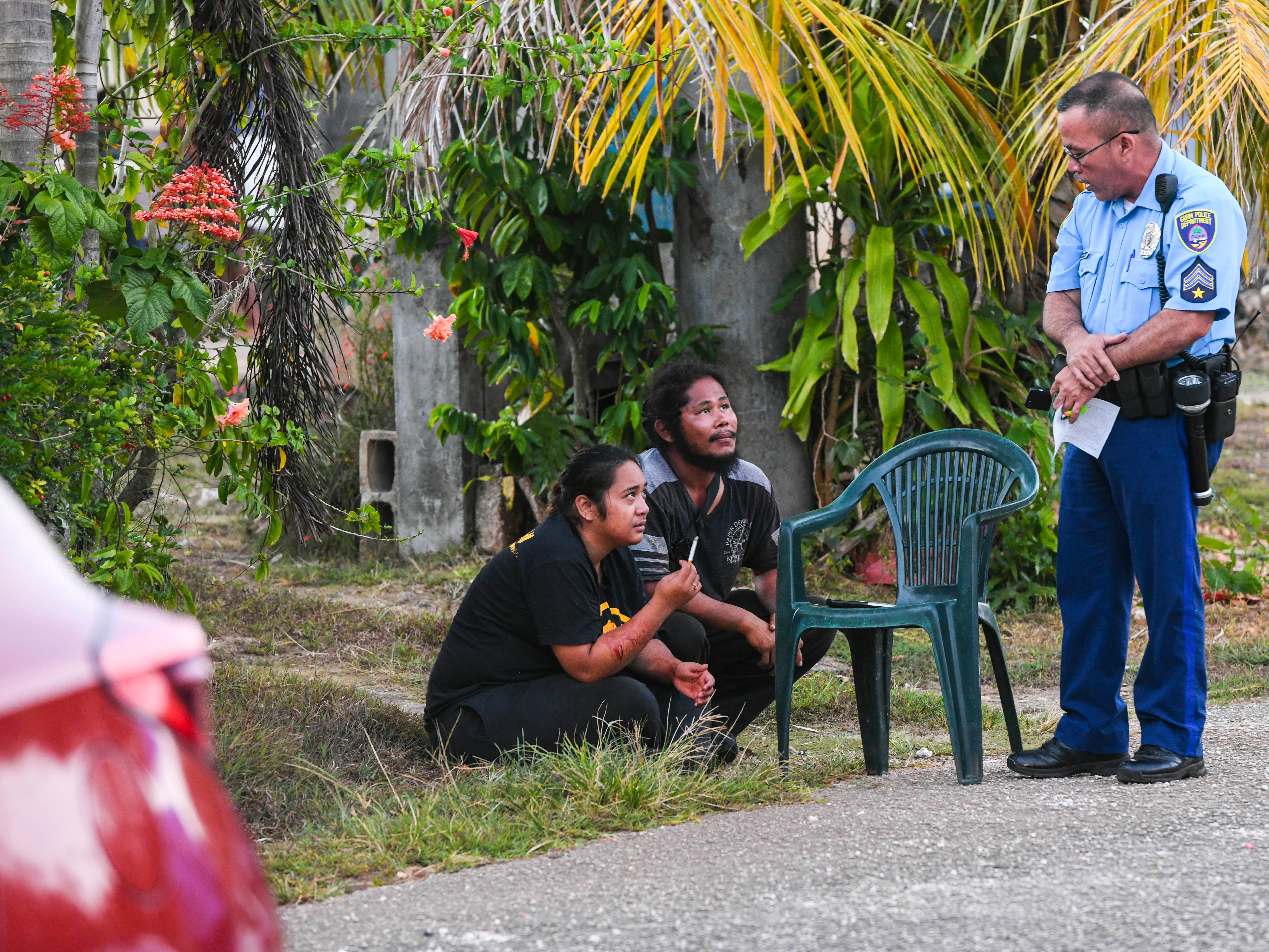 Guam Police Department Officer Jeb Santo Tomas speaks with Ewily Risa, seated left, and another individual, during a fatal auto-pedestrian incident in Dededo on the evening of Wednesday, May 7, 2019. Four-year-old Jericho Zion David, died after being struck in front of his family's home, by a Red Toyota Corolla driven by Risa,