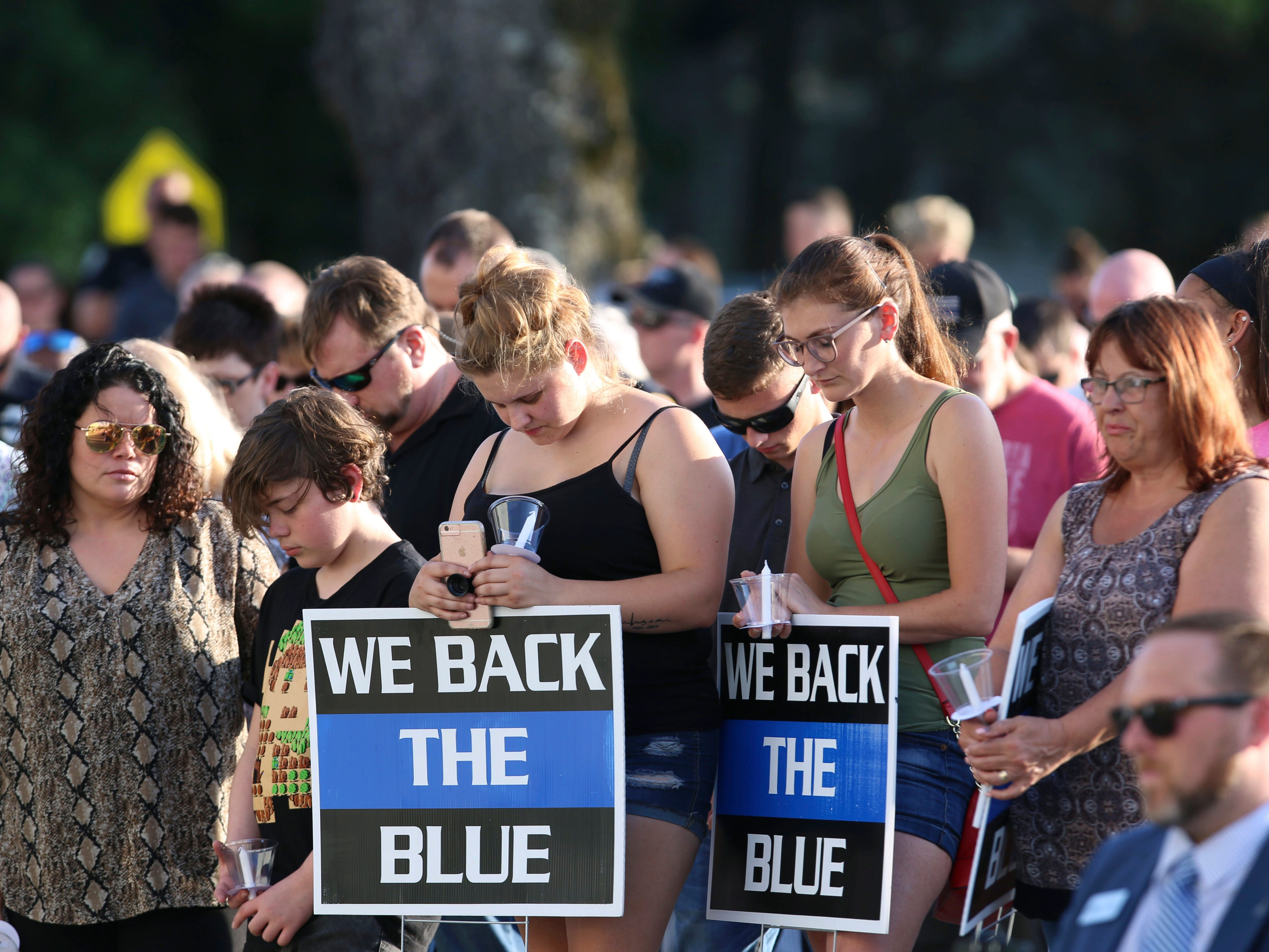 Dozens of people bowed their heads to honor fallen Biloxi police officer Robert McKeithen during a prayer vigil on Tuesday, May 7, 2019, outside the police department in Biloxi, Miss. A Biloxi police officer, McKeithen died after being shot multiple times in the parking lot of the Biloxi Police Department, Sunday night.