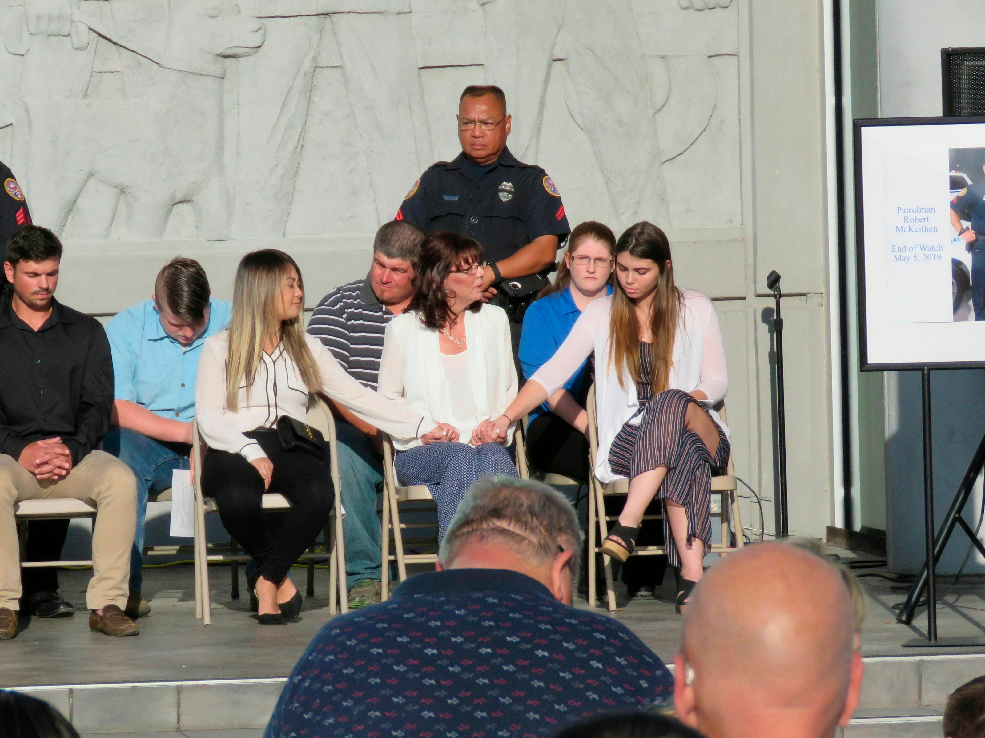 Pamela McKeithen, seated front second from right, sits with her family onstage during a memorial service for her husband, Biloxi Police Patrolman Robert McKeithen, on Tuesday, May 7, 2019, outside the city's Public Safety Center, where the police department is located in Biloxi, Miss. Patrolman Robert McKeithen was killed Sunday night in the parking lot.