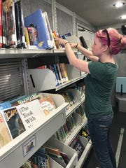 Evanne Flanders, special needs programming and outreach specialist for the Madison County Library System, straightens books in the bookmobile.