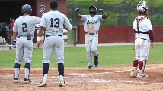 In this file photo, Dezmond Chumley crosses home plate as teammates Wesley Reyes (2) and Jaylyn Williams (13) wait to congratulate him.