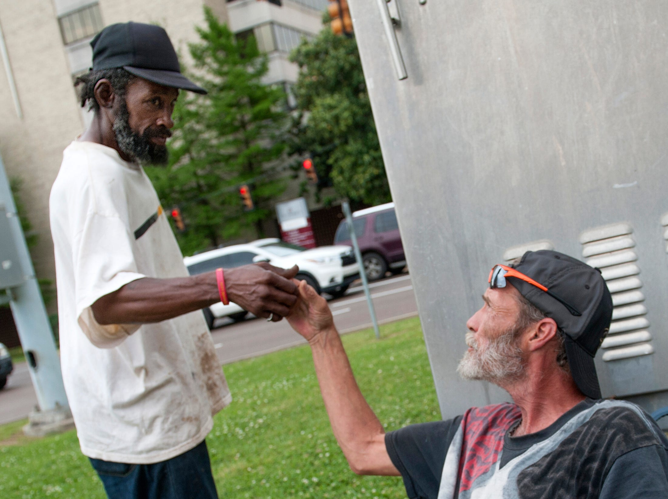 When he got the money he needed to pay for food for the day, Dan, left, walked across the street to let Jeffery know he was done and that the corner was his to work.