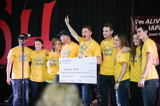 "The family of Grant House stands on stage with with a large check totaling the $208,000 raised Friday evening during the annual ""I'm Happy and I'm Alive"" fundraiser."