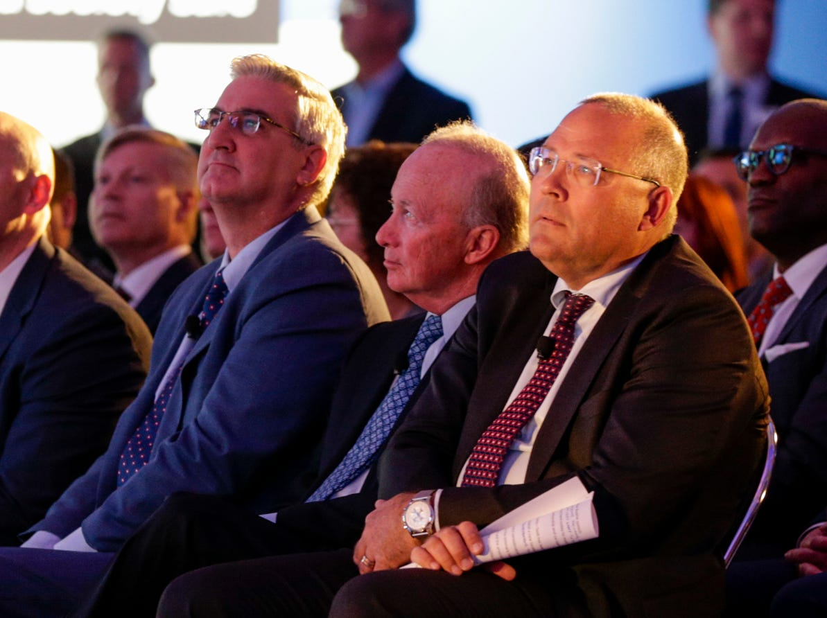 From left, Gov. Eric Holcomb, Purdue University president Mitch Daniels and Saab President and CEO Hakan Buskhe listen during an announcement for a new Saab jet plant in West Lafayette, part of a $1 billion west campus plan, Wednesday, May 8, 2019 at the Purdue University airport in West Lafayette.