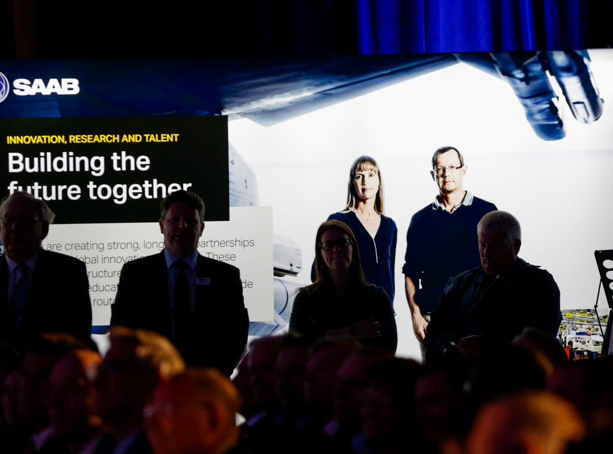 A Saab promotional banner lights audience members as Purdue University president Mitch Daniels speaks during an announcement for a new Saab jet plant in West Lafayette, part of a $1 billion west campus plan, Wednesday, May 8, 2019 at the Purdue University airport in West Lafayette.