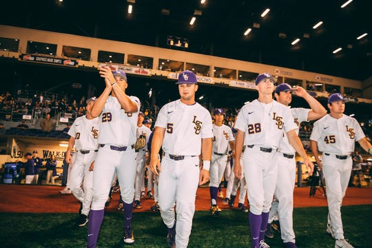 LSU baseball players Chase Costello (No. 29), Drew Bianco (No. 5), Devin Fontenot (No. 28), and Braden Doughty (No. 45) walk on the field with their teammates.