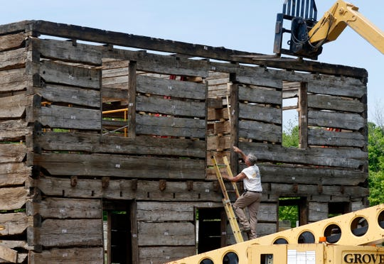 Workers from Shaw & Holter rebuild a log-framed house Tuesday morning, May 7, 2019, at Smeck Park near Baltimore. The Beck-Reef house was deconstructed at its location on Rainbow Drive and is now being rebuilt in the park after being donated to the county parks district by the owners.