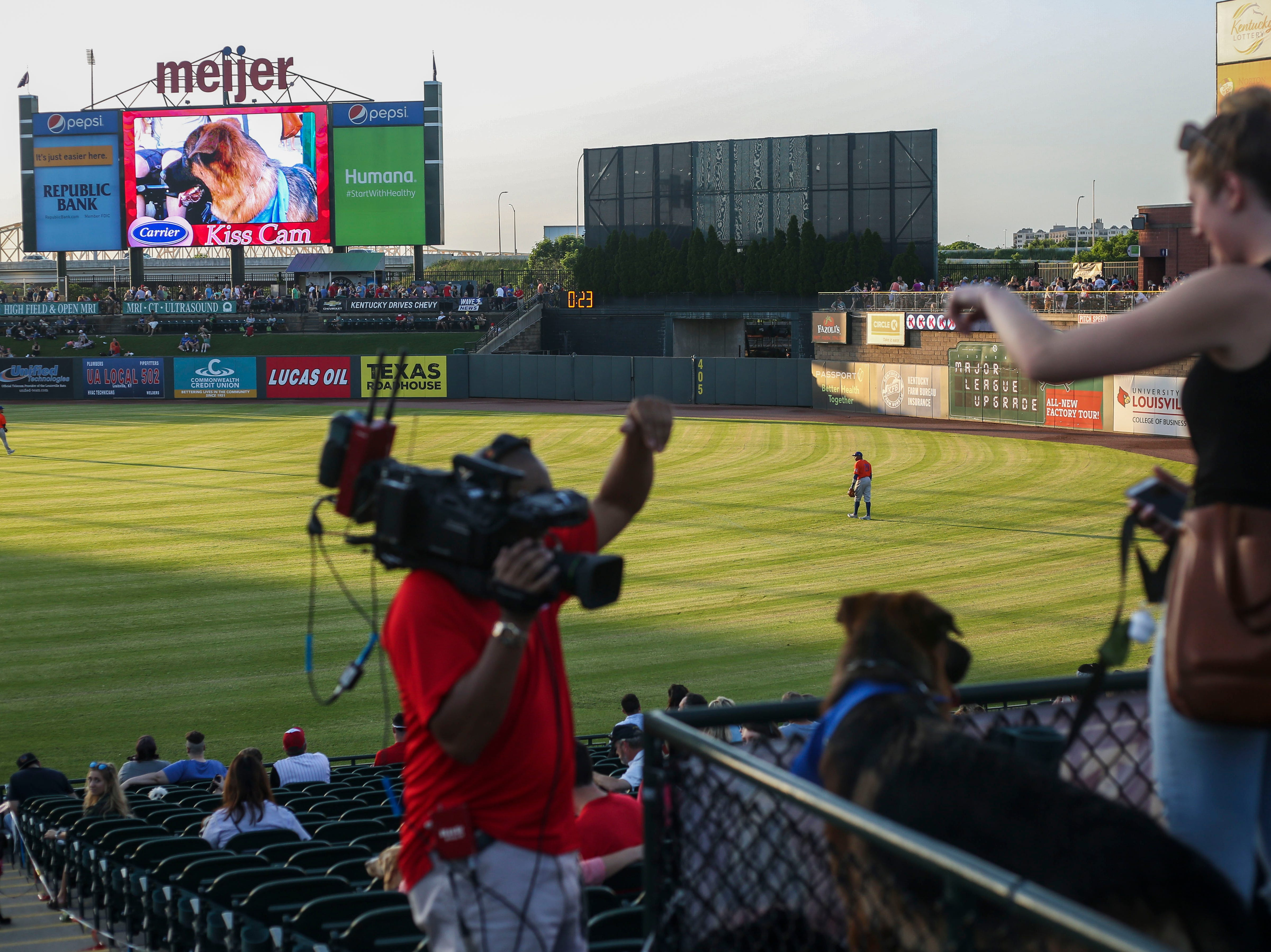 A cameraman attempts to get a dog to look into the Kiss Cam during the Louisville Bats v. Syracuse Mets game during Dog Day Nights at Louisville Slugger Field in downtown Louisville, Ky. on Tuesday, May 7, 2019.