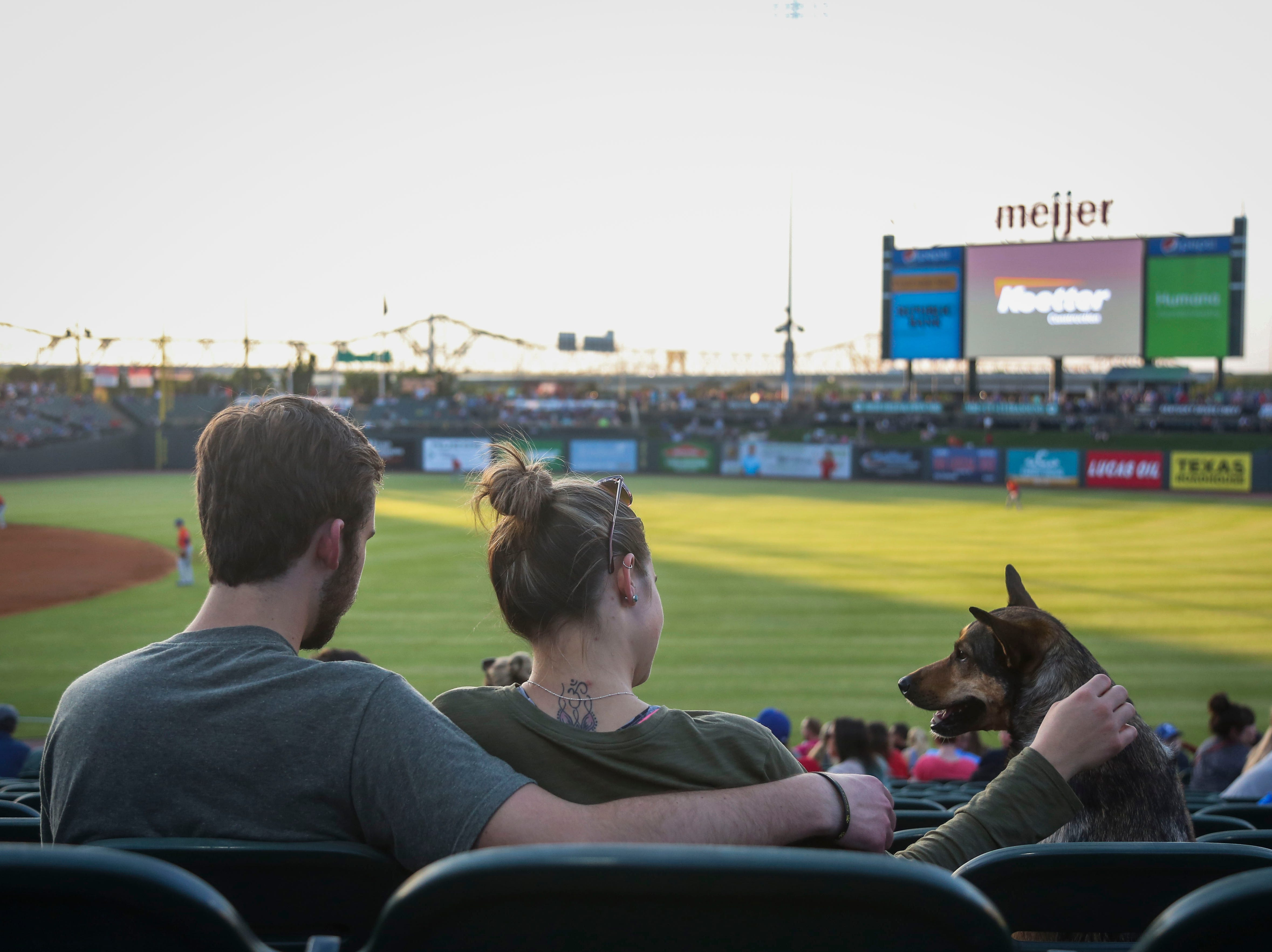 Chris Mattingly, left, Savanah Ruhs, middle, and Nova watch the Louisville Bats v. Syracuse Mets game during Dog Day Nights at Louisville Slugger Field in downtown Louisville, Ky. on Tuesday, May 7, 2019.