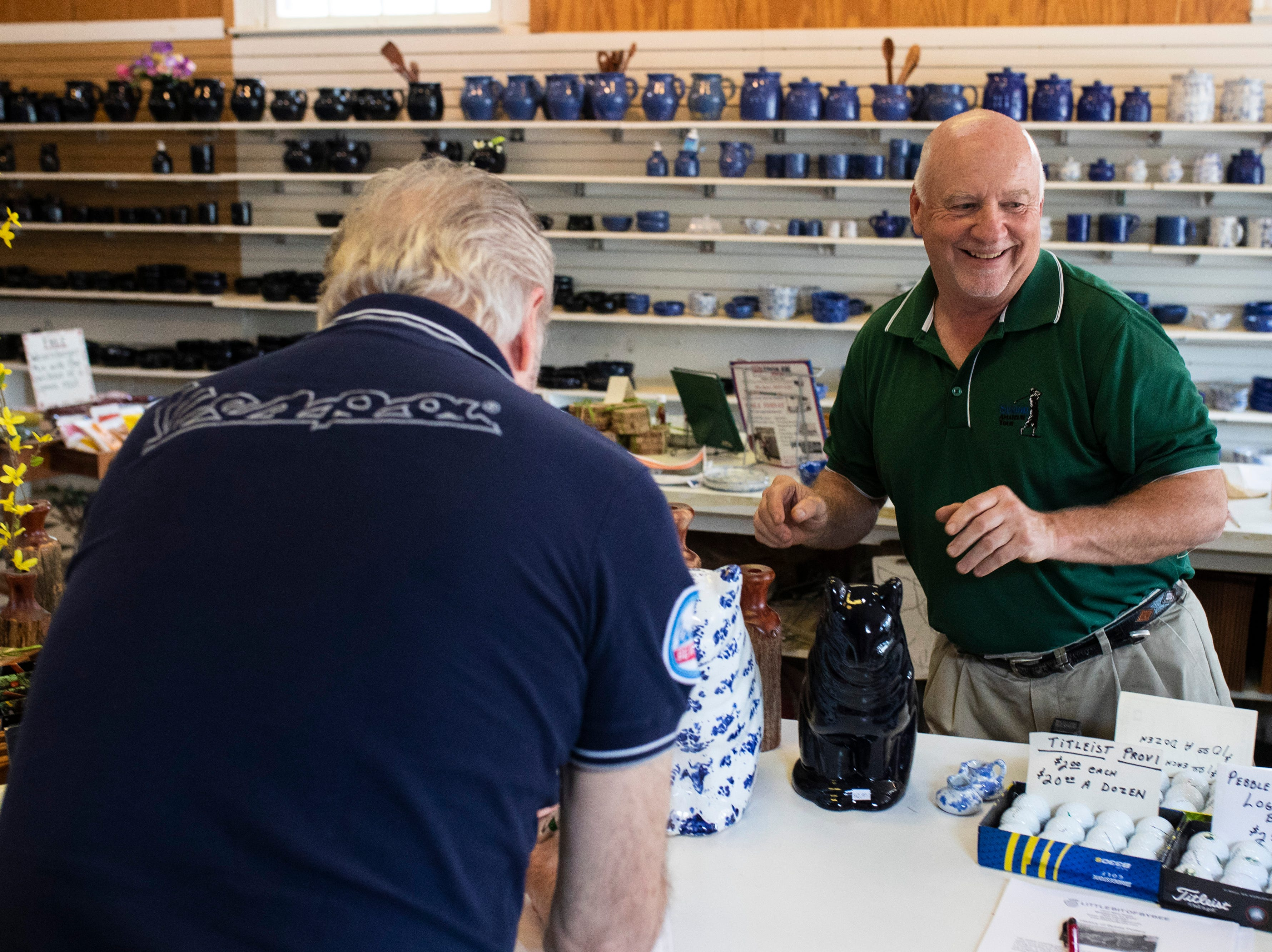 Ron Stambaugh assist a customer inside the Little Bit of Bybee pottery shop in the Middletown neighborhood. May 8, 2019