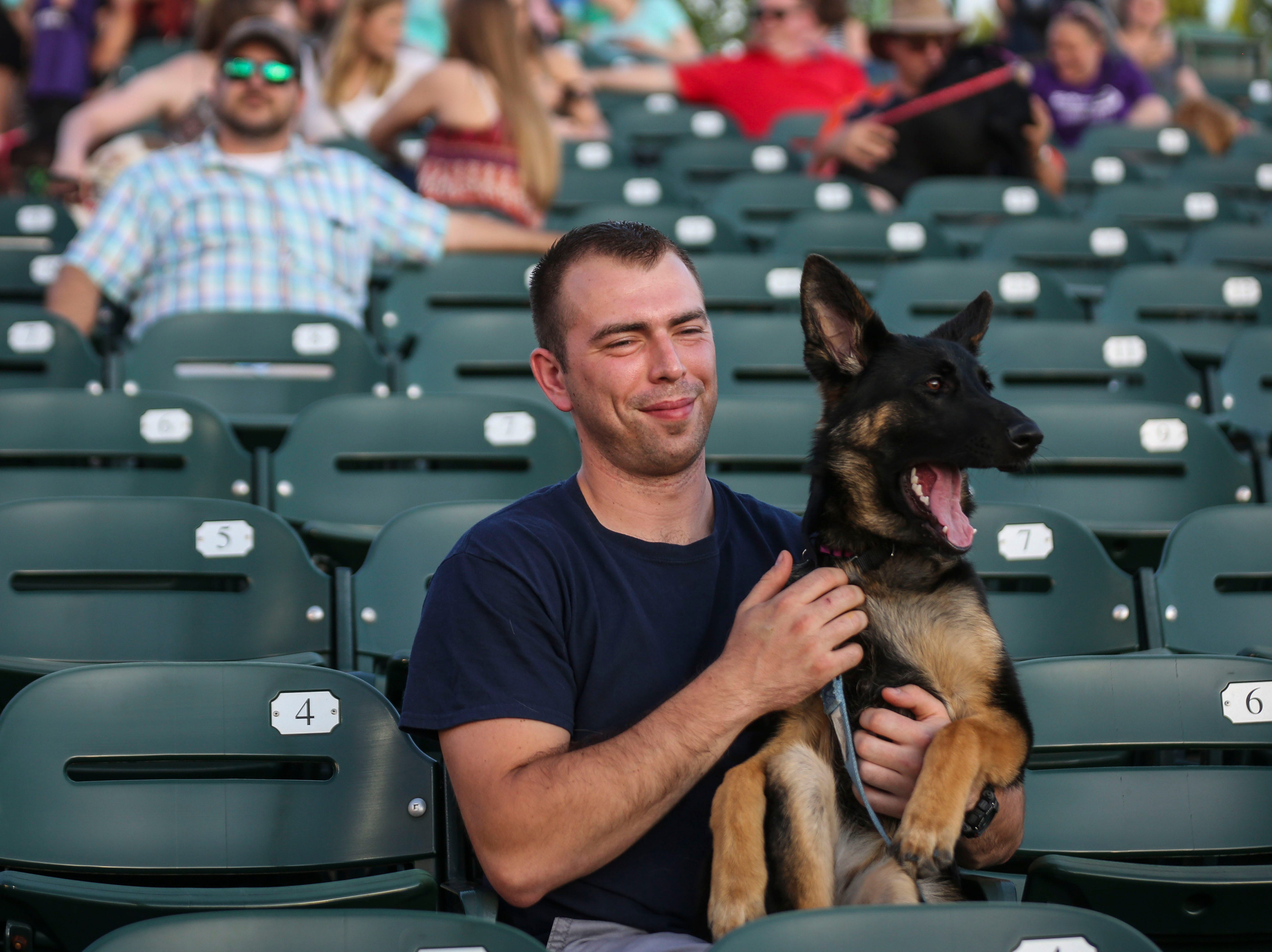 Lance Beckner sits with his German Shepard Kyra during the Louisville Bats v. Syracuse Mets game during Dog Day Nights at Louisville Slugger Field in downtown Louisville, Ky. on Tuesday, May 7, 2019.