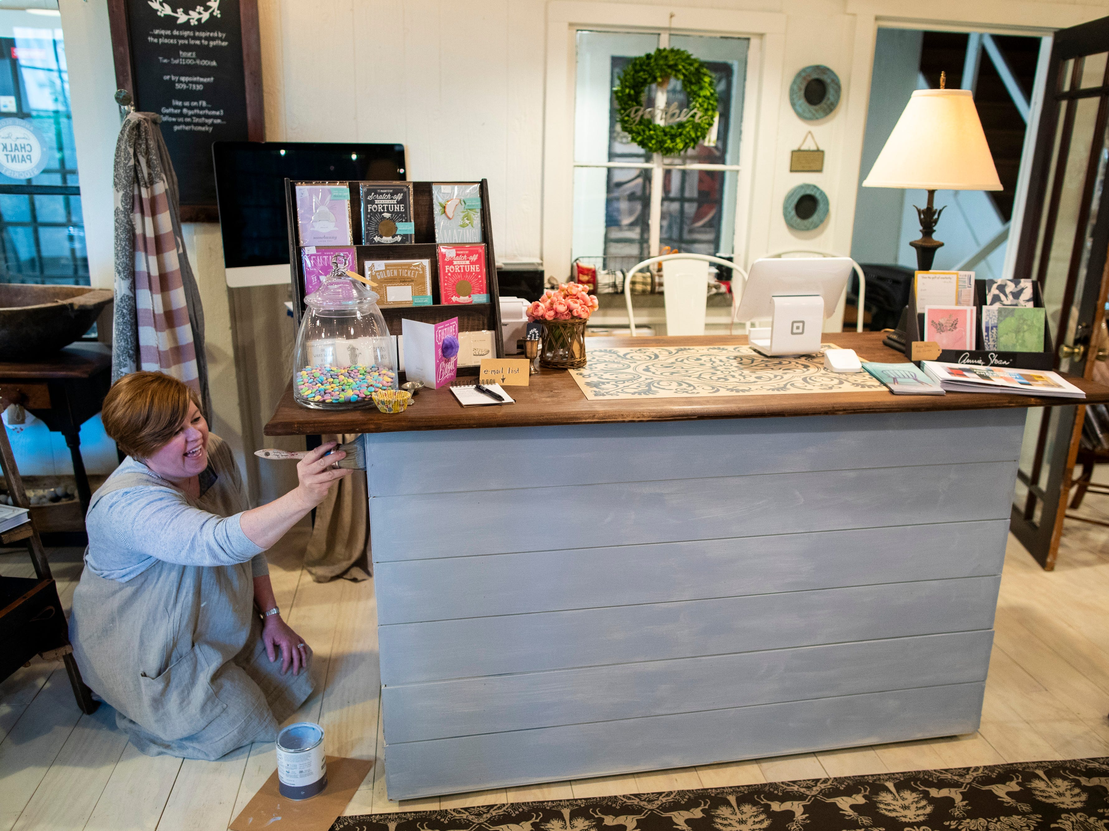 """Beth Myers works on using Annie Sloan chalk paint to freshen up her register area inside Gather, Myers' home decor and DIY shop in the Middletown neighborhood. """"We've been around for two years and hold workshops a couple times a month,"""" Myers said. May 8, 2019"""