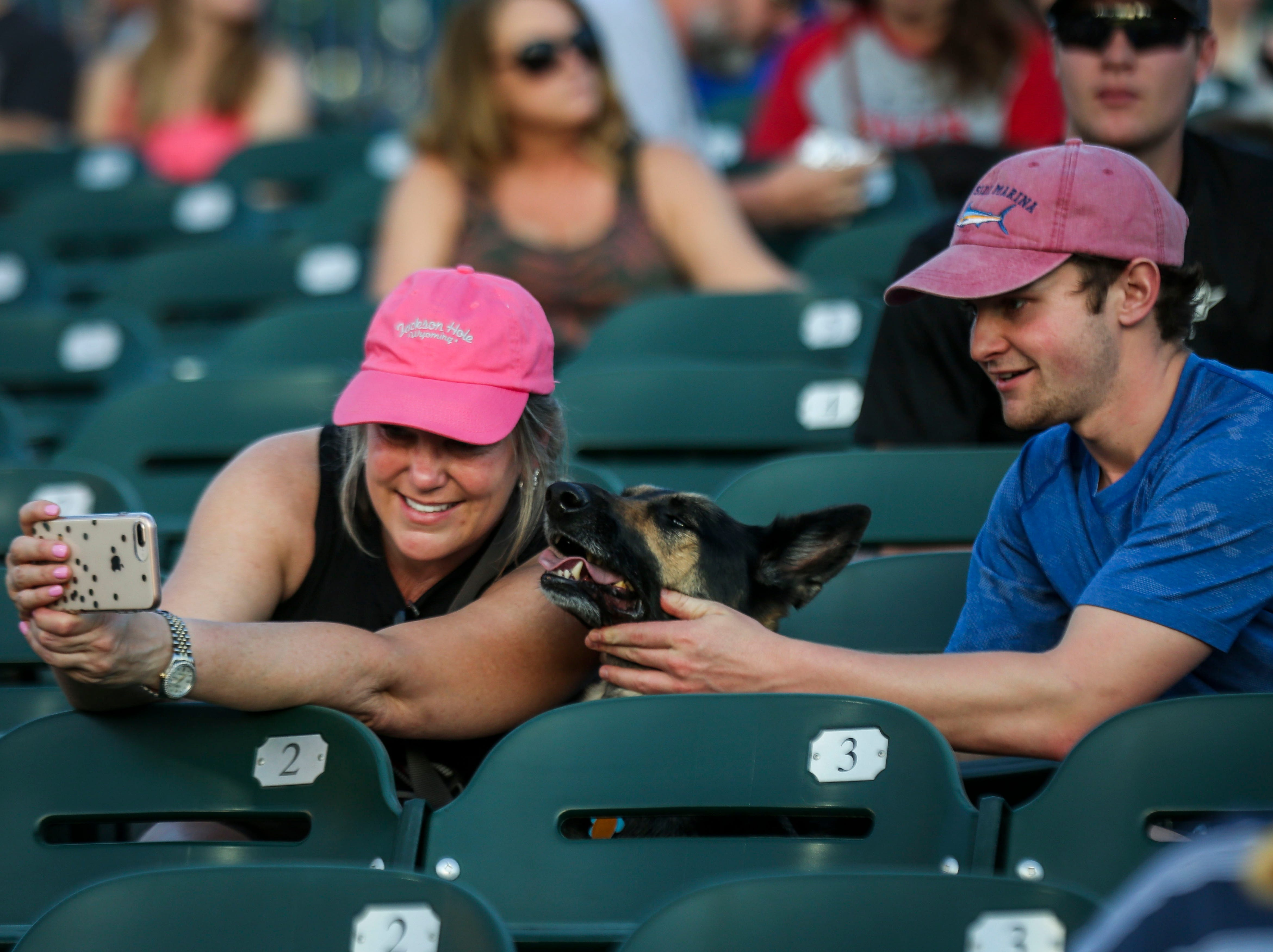 Mitchell Gordon helps Angela Gordon take a selfie with Heidi the German Shepard during the Louisville Bats v. Syracuse Mets game during Dog Day Nights at Louisville Slugger Field in downtown Louisville, Ky. on Tuesday, May 7, 2019.