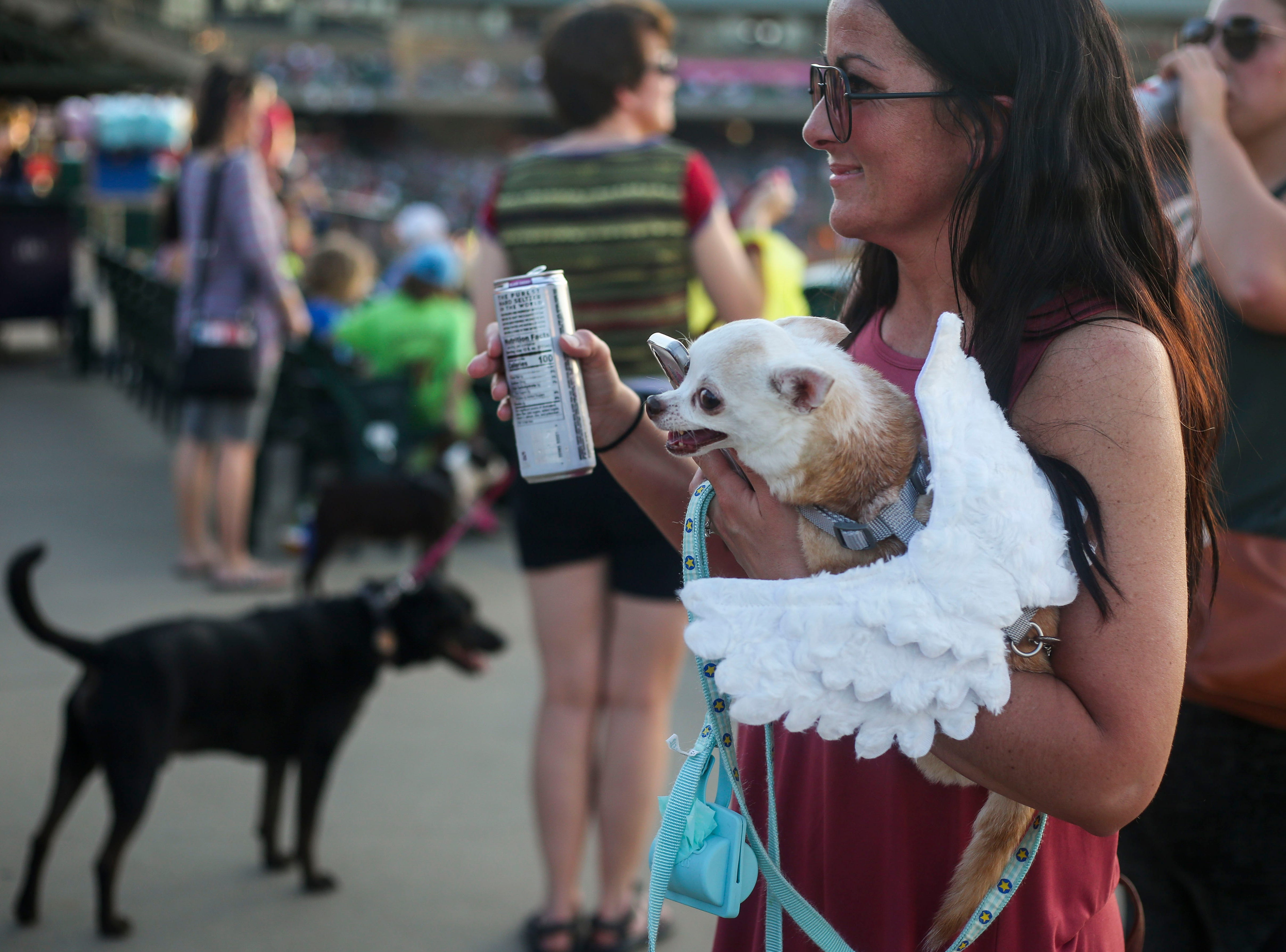 Megan Wolfe carries Lola during the Louisville Bats v. Syracuse Mets game during Dog Day Nights at Louisville Slugger Field in downtown Louisville, Ky. on Tuesday, May 7, 2019.