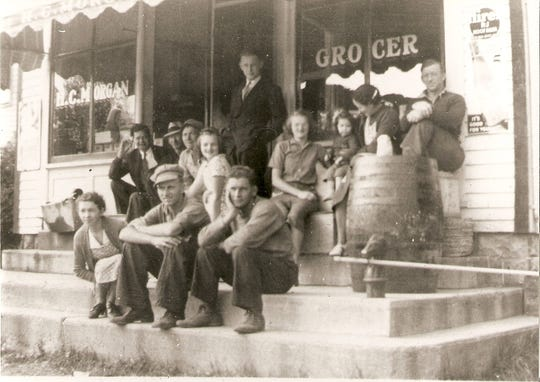 Outside the General Store in Clarks Mills — the Clover Farm Store. Pictured are, front row, from left: Ann Rolland, Clem Rolland and Harold Pritzl; and second row, from left: Cliffford (Kink) Polansky, Jerry Rolland, Joseph Lemberger, Anna Mae Morgan Hartman, Jeanette Morgan Hein, Shirley Rolland Kolar, Mayme Rolland and Harold Morgan. Standing is Lawrence Brennen. Image dated 1938.